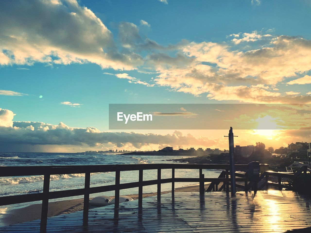 cloud - sky, sky, water, sunset, beauty in nature, scenics - nature, railing, nature, tranquil scene, no people, tranquility, architecture, built structure, wood - material, outdoors, sea, idyllic, sunlight, orange color, wooden post