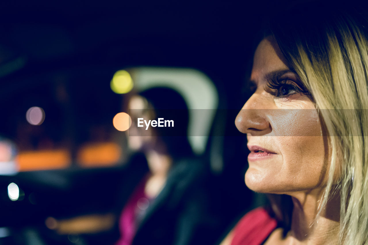headshot, portrait, real people, women, adult, focus on foreground, one person, looking, young adult, young women, side view, mode of transportation, lifestyles, close-up, motor vehicle, car, night, beautiful woman, profile view, contemplation, hairstyle, human face