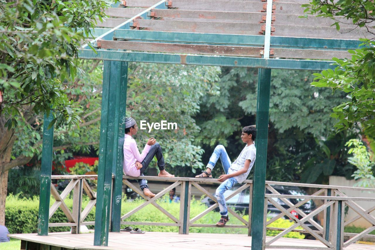Teenage Boys Sitting On Railing In Gazebo At Park