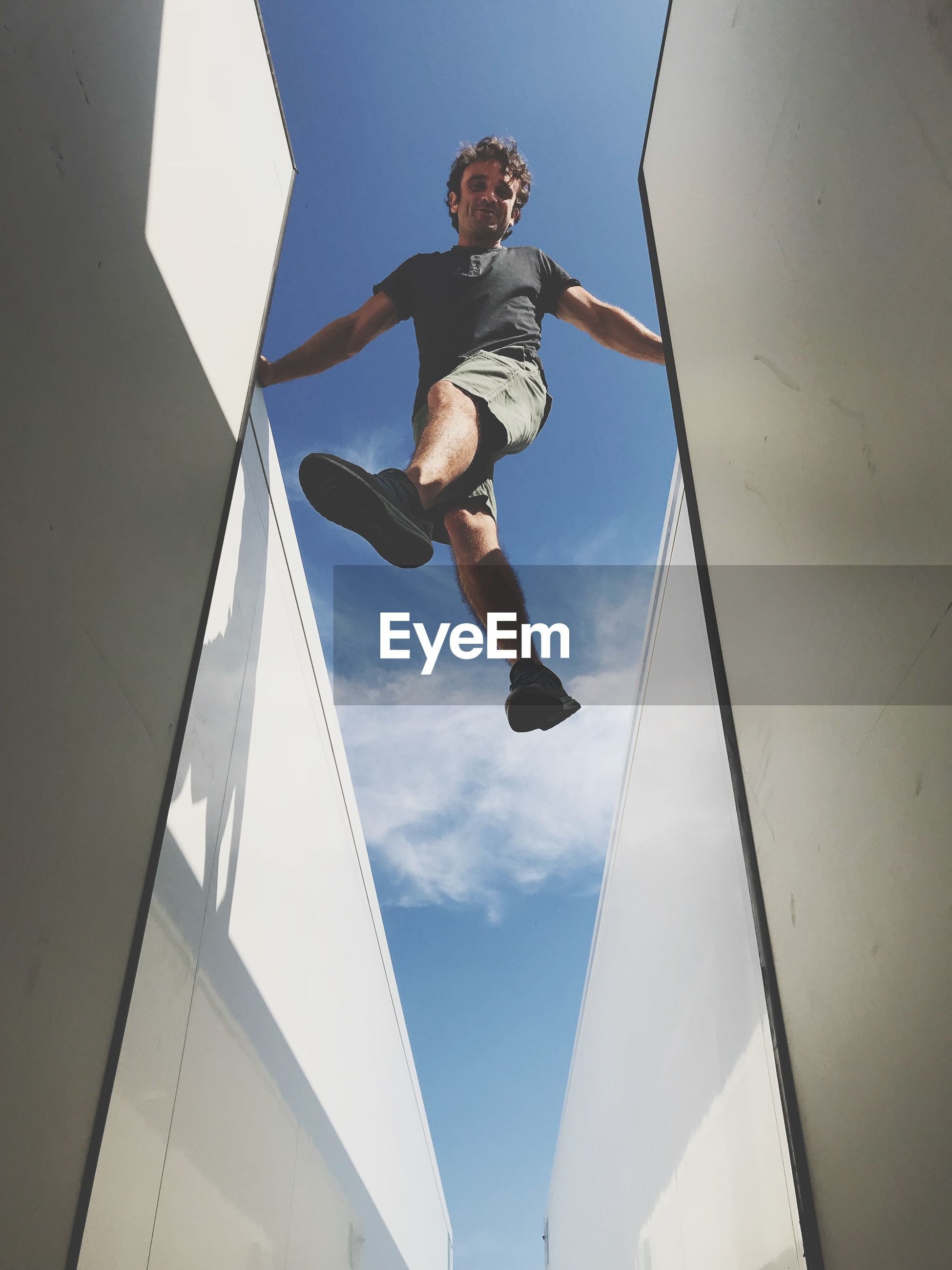Low angle view of man jumping amidst buildings against sky