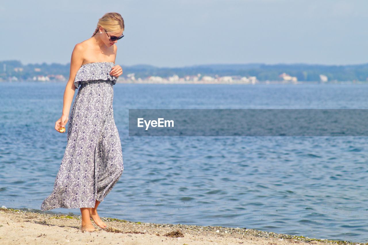 Woman Walking On Shore At Beach Against Sky