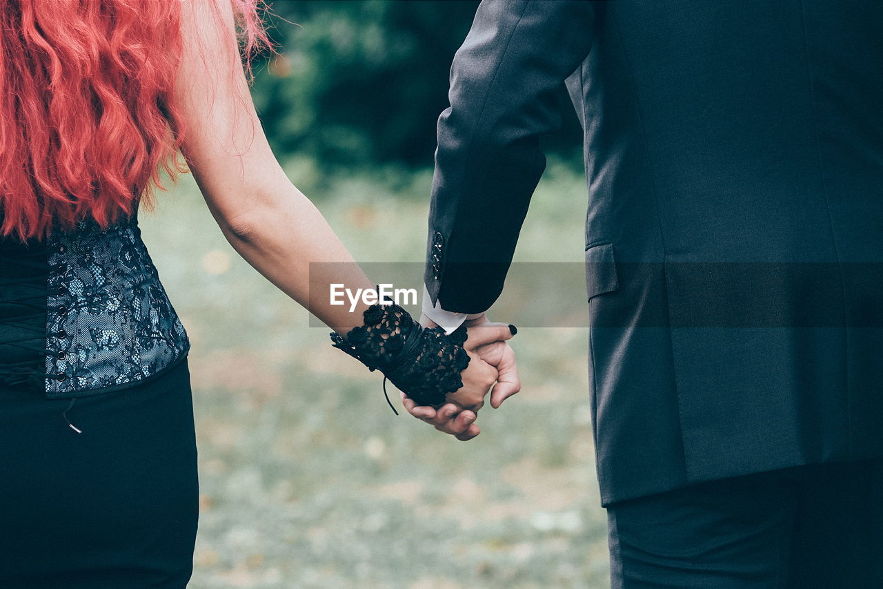 Midsection Of Wedding Couple Holding Hands
