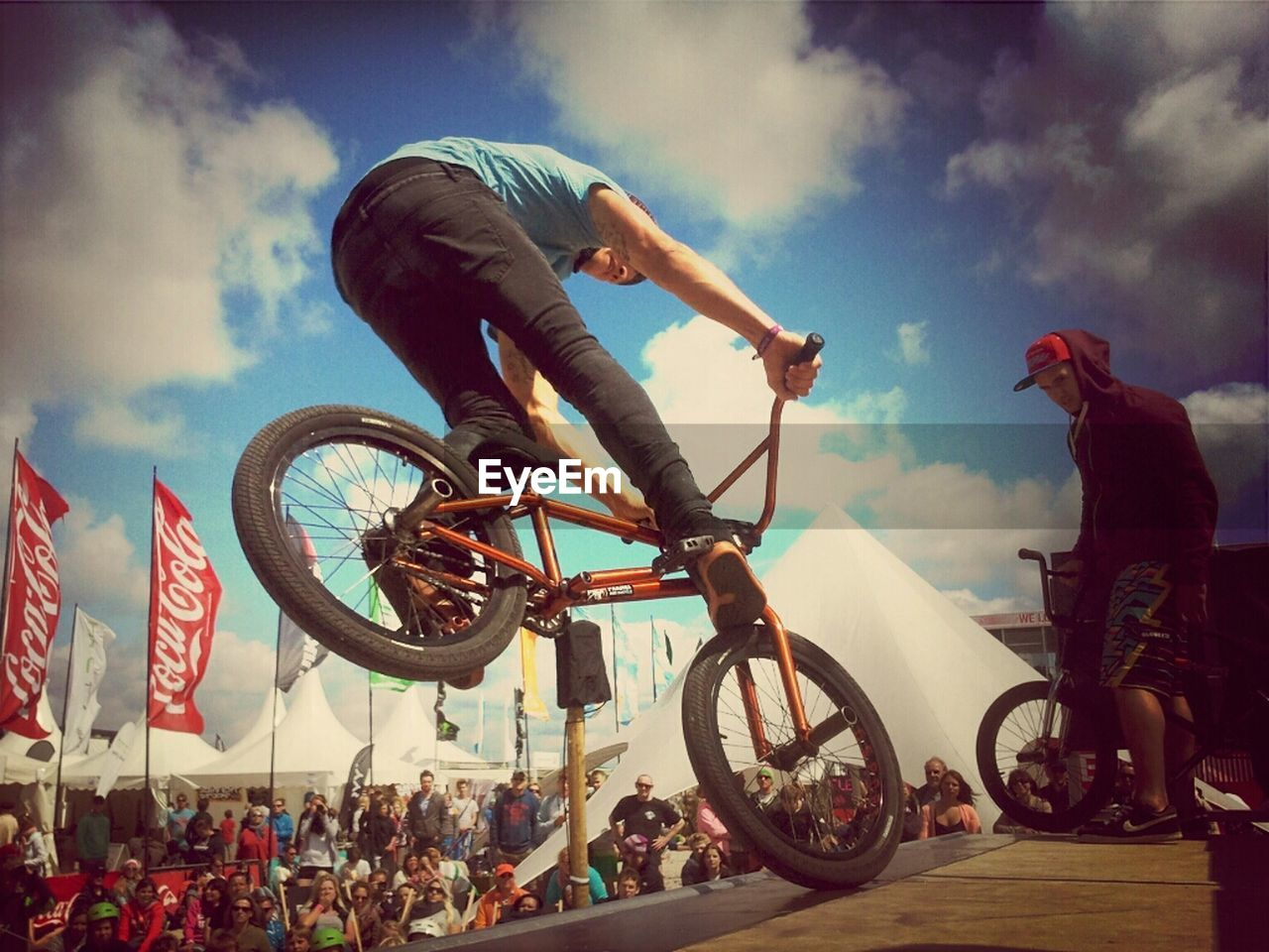 bicycle, transportation, real people, mode of transport, sky, men, cycling, leisure activity, riding, fun, day, outdoors, bmx cycling, land vehicle, lifestyles, sport, extreme sports, motion, low angle view, adventure, helmet, women, stunt, crowd, biker, people