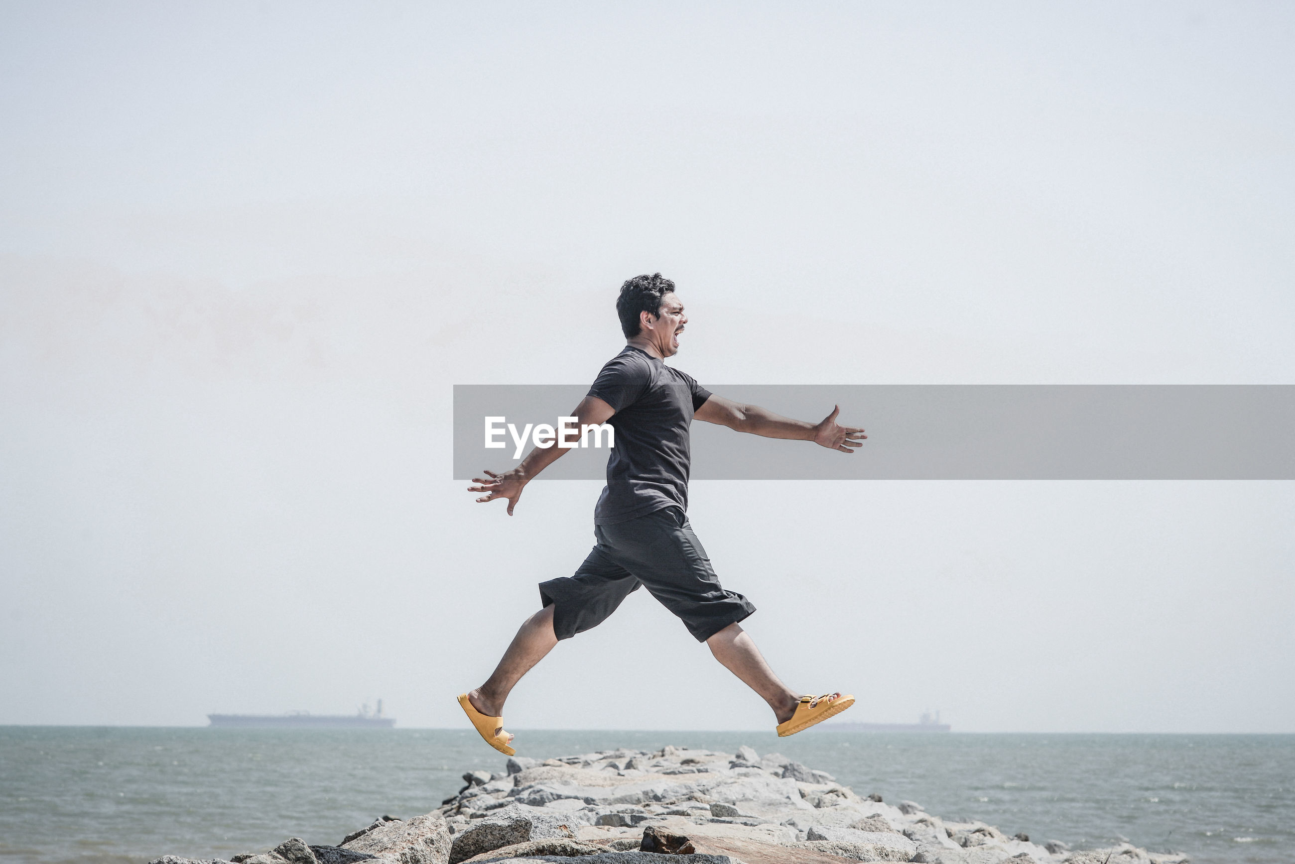 Full length of man jumping on rock at beach against sky