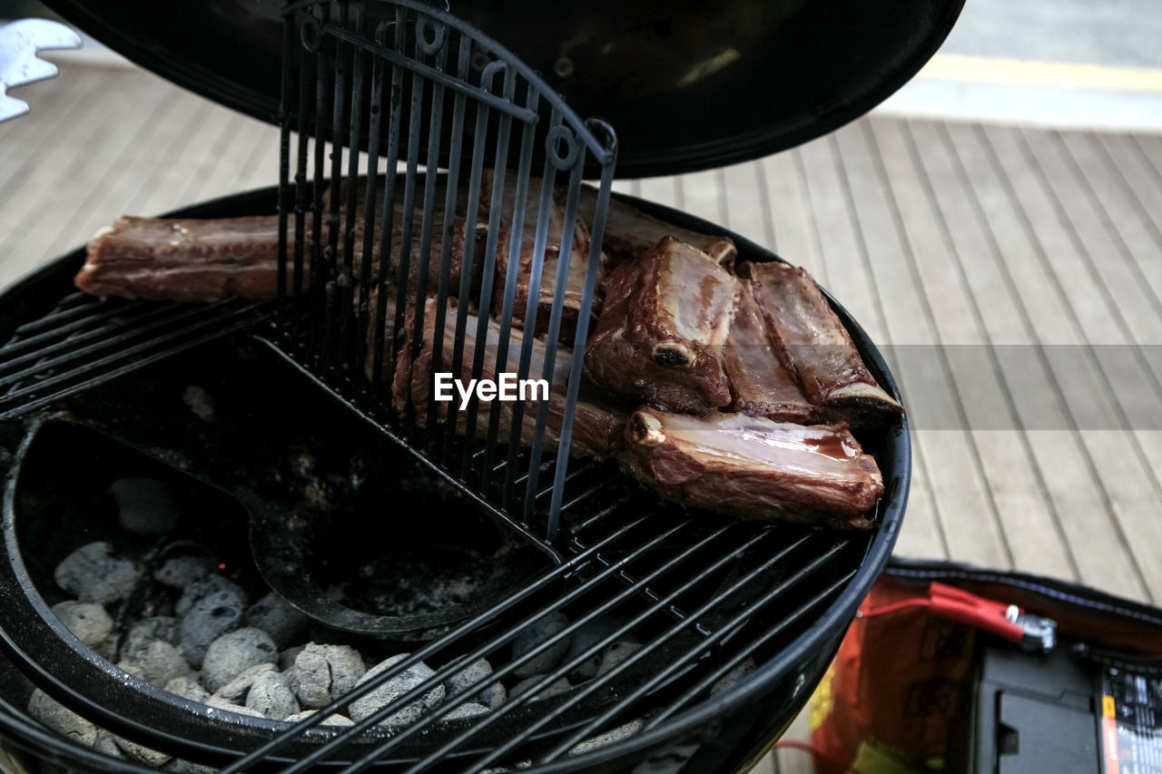 High angle view of beef ribs grilling on barbeque grill