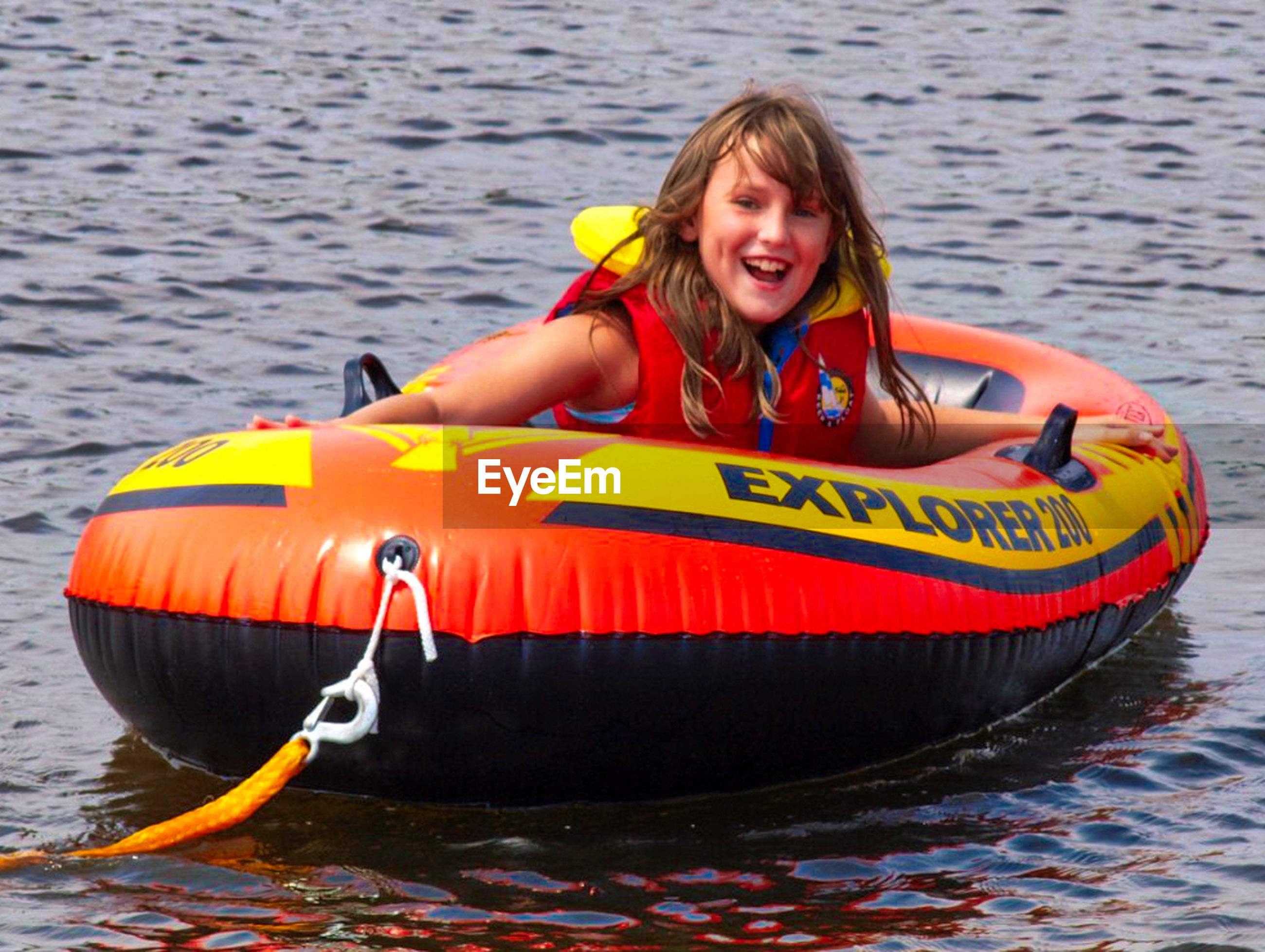 water, life jacket, nautical vessel, oar, smiling, kayak, looking at camera, portrait, one person, leisure activity, floating on water, day, yellow, happiness, outdoors, blond hair, real people, lake, adventure, inflatable raft, young adult, nature, adult, adults only, people