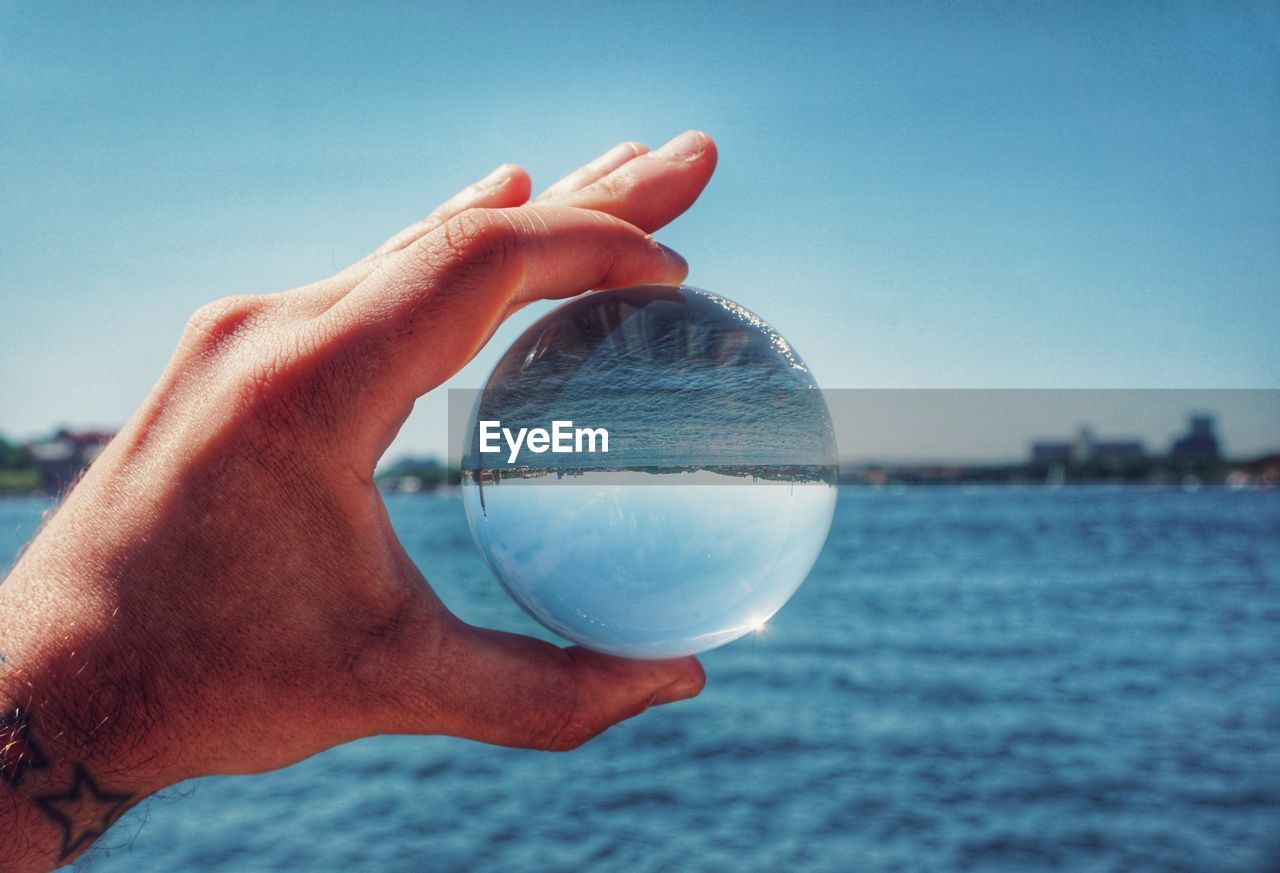 human hand, hand, one person, human body part, water, holding, sky, sphere, crystal ball, focus on foreground, unrecognizable person, sea, nature, transparent, finger, real people, human finger, personal perspective, body part, outdoors