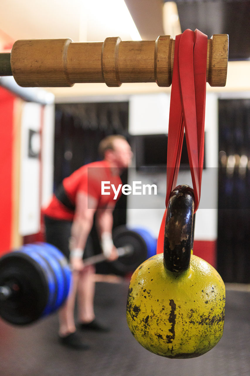 Kettlebell Hanging On Wood While Man Exercising In Background