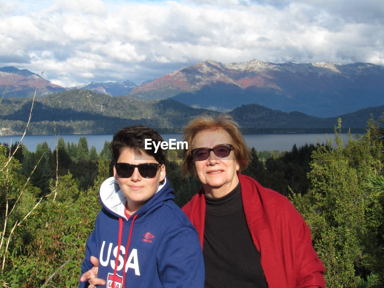 Portrait of mother and son standing at lakeshore against mountains