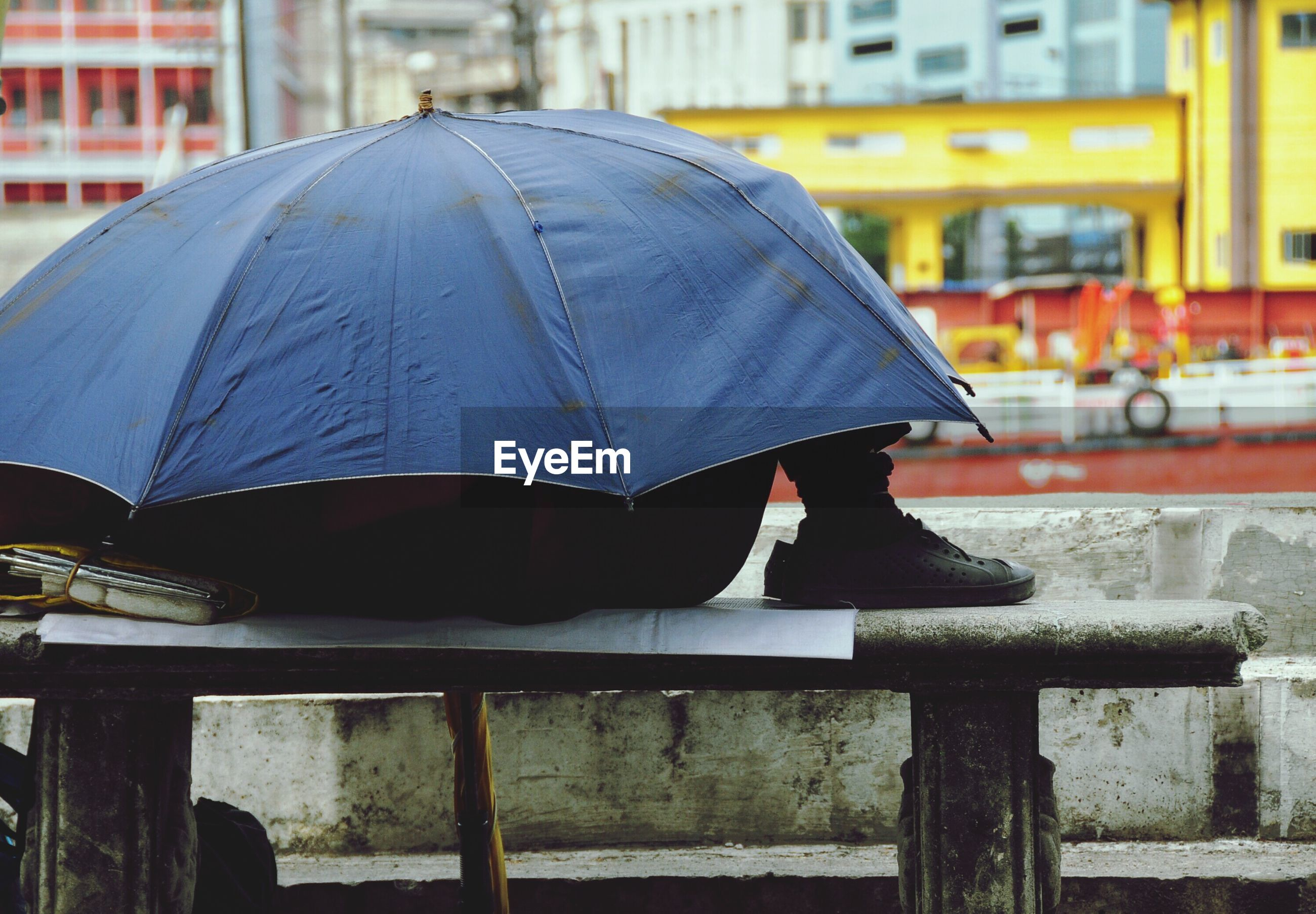 Side view of man resting below umbrella on bench