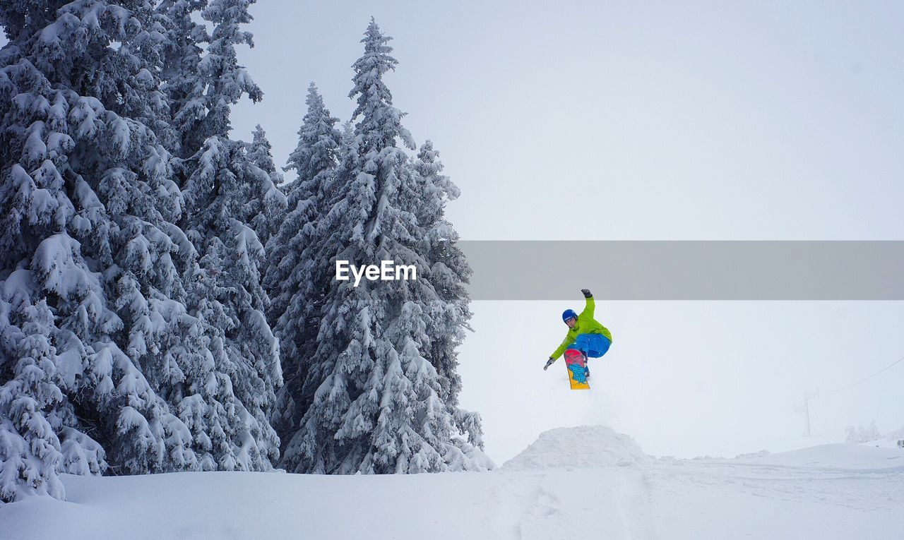 snow, cold temperature, winter, leisure activity, full length, weather, lifestyles, adventure, fun, real people, white color, nature, outdoors, sport, one person, day, beauty in nature, motion, vacations, mountain, tree, scenics, warm clothing, extreme sports, clear sky, snowboarding, ski holiday, sky, people