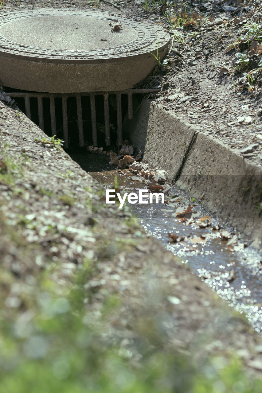 water, nature, day, no people, outdoors, flowing water, selective focus, architecture, environmental issues, sewage, solid, sewer, sunlight, gutter, built structure, high angle view, focus on background, motion, wall - building feature, flowing, pollution, concrete