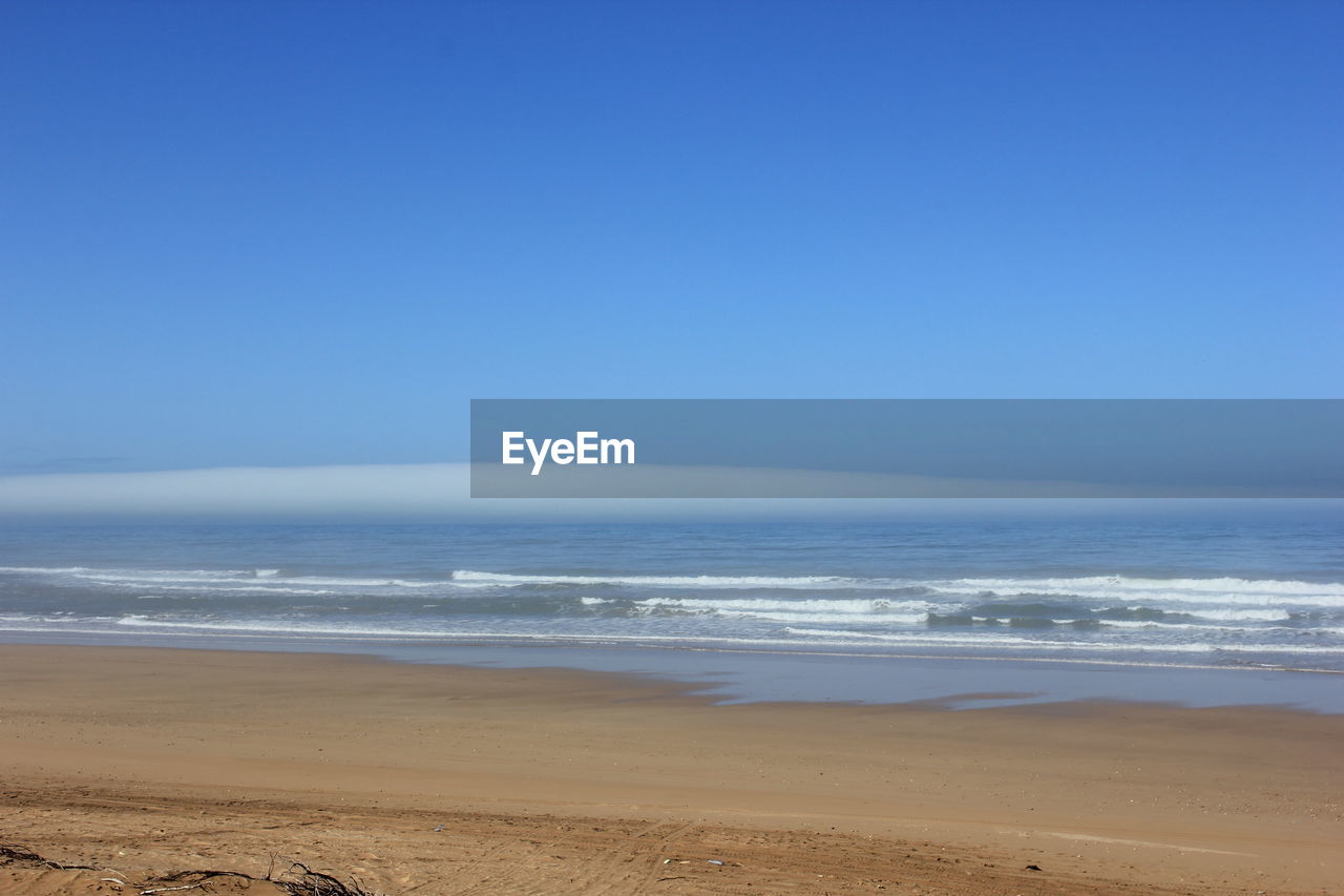 sea, land, water, beach, sky, scenics - nature, beauty in nature, horizon over water, horizon, copy space, tranquility, blue, sand, clear sky, motion, tranquil scene, nature, non-urban scene, no people, outdoors, flowing water