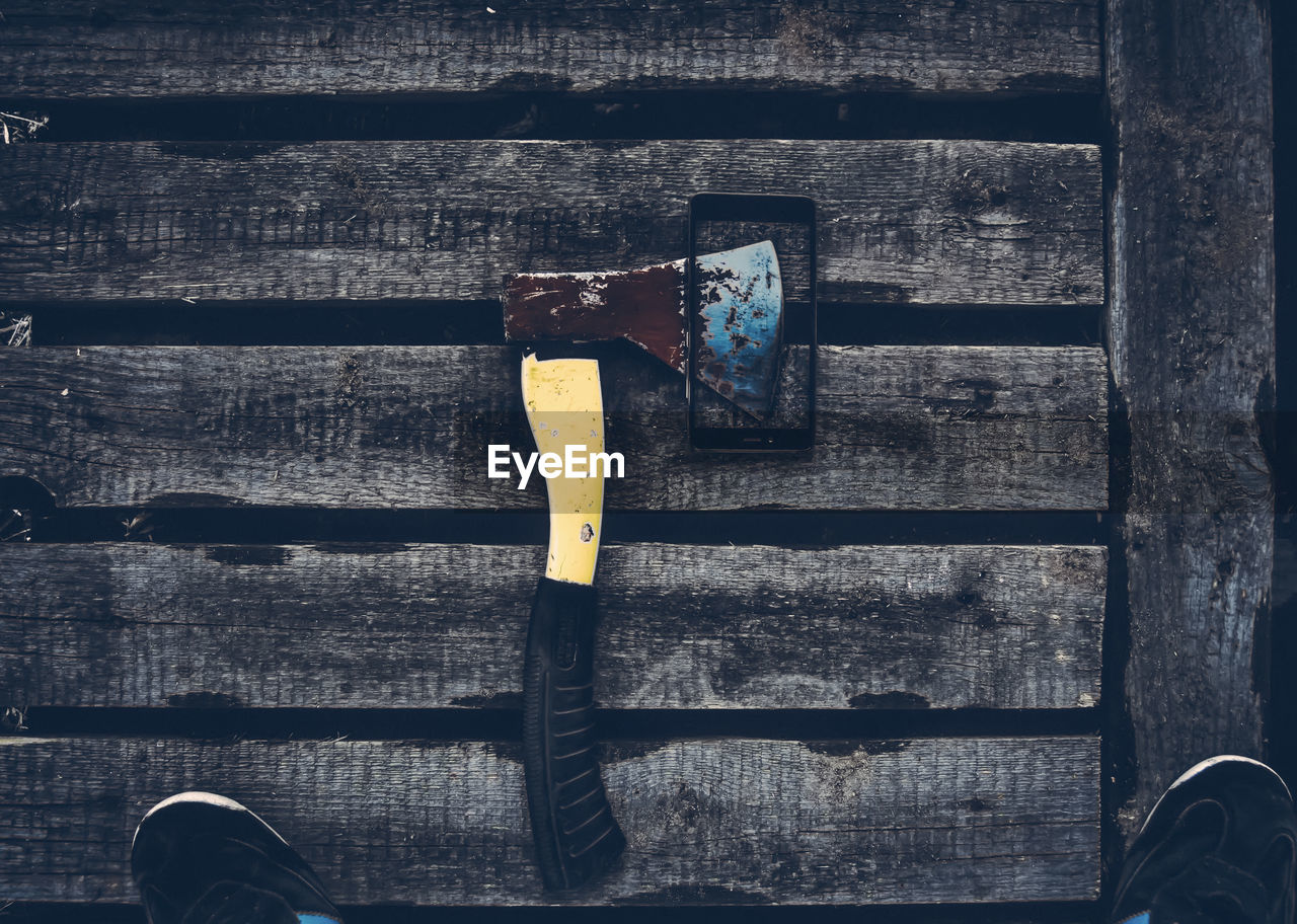 High Angle View Of Broken Mobile Phone Along With Axe On Wooden Platform