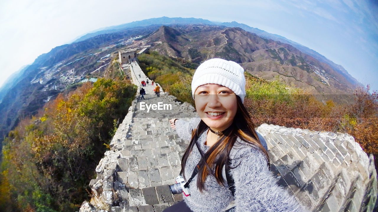 Fish-eye lens portrait of smiling woman against mountain range