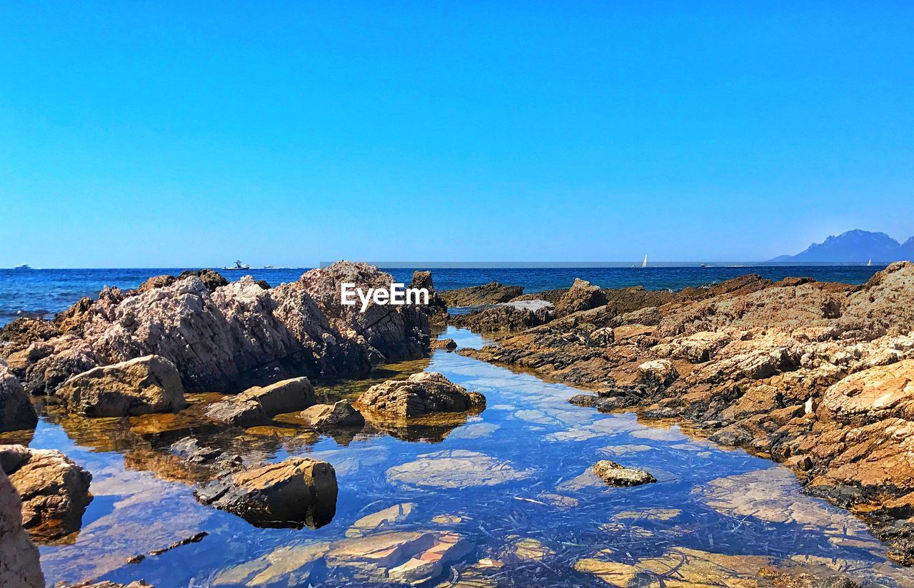 sea, sky, water, rock, blue, scenics - nature, rock - object, clear sky, copy space, beauty in nature, solid, tranquility, tranquil scene, horizon over water, nature, horizon, day, beach, land, no people, rocky coastline, groyne