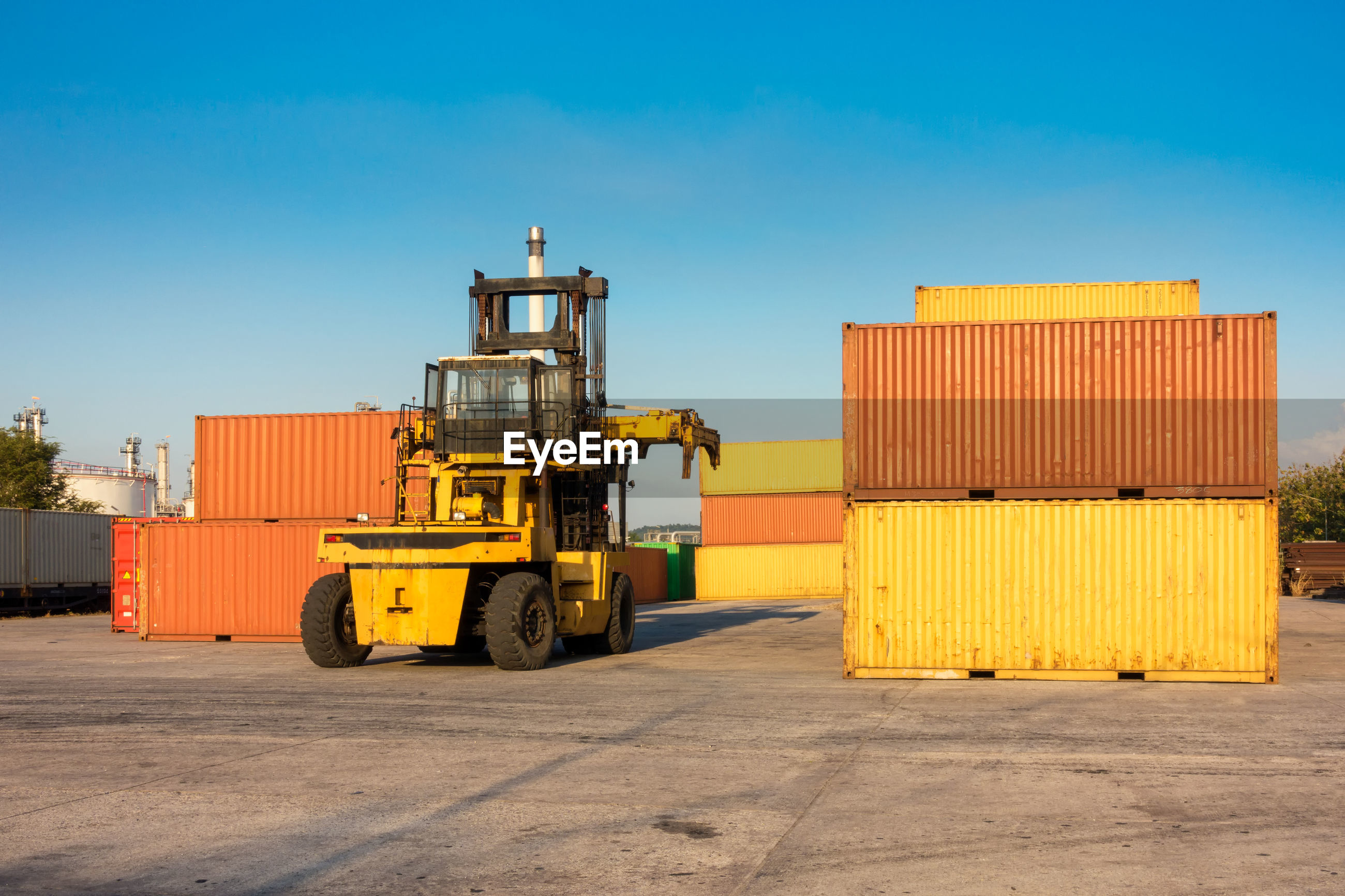 Machinery amidst cargo containers at dock against clear blue sky
