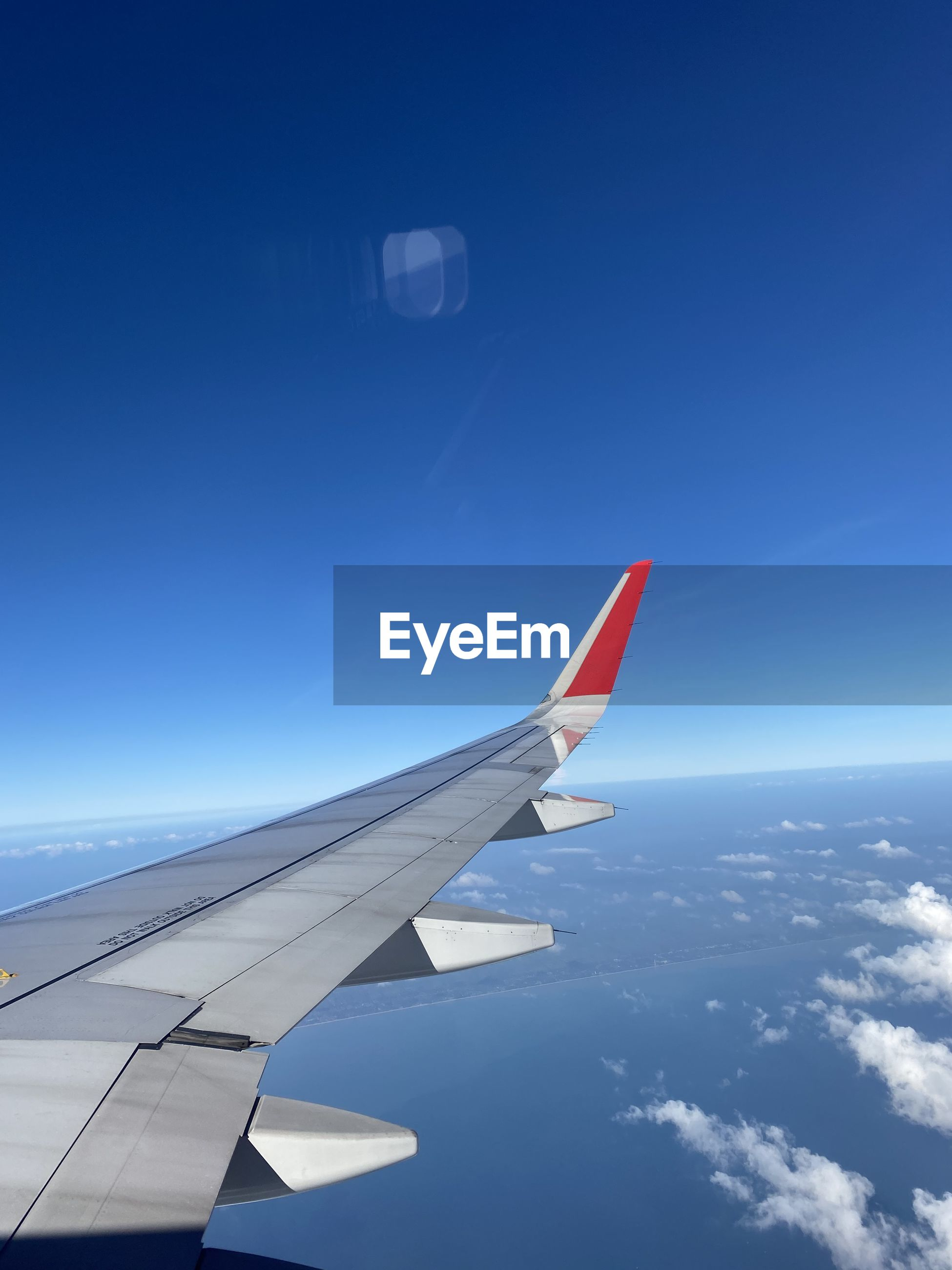 VIEW OF AIRPLANE FLYING OVER BLUE SKY