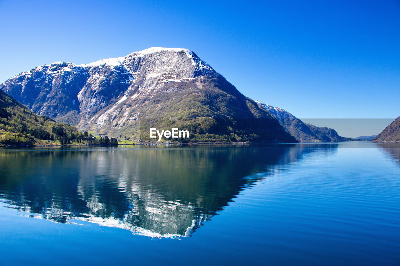 mountain, beauty in nature, tranquil scene, scenics - nature, tranquility, blue, water, sky, reflection, clear sky, lake, mountain range, nature, idyllic, non-urban scene, waterfront, day, no people, cold temperature, outdoors, snowcapped mountain, formation