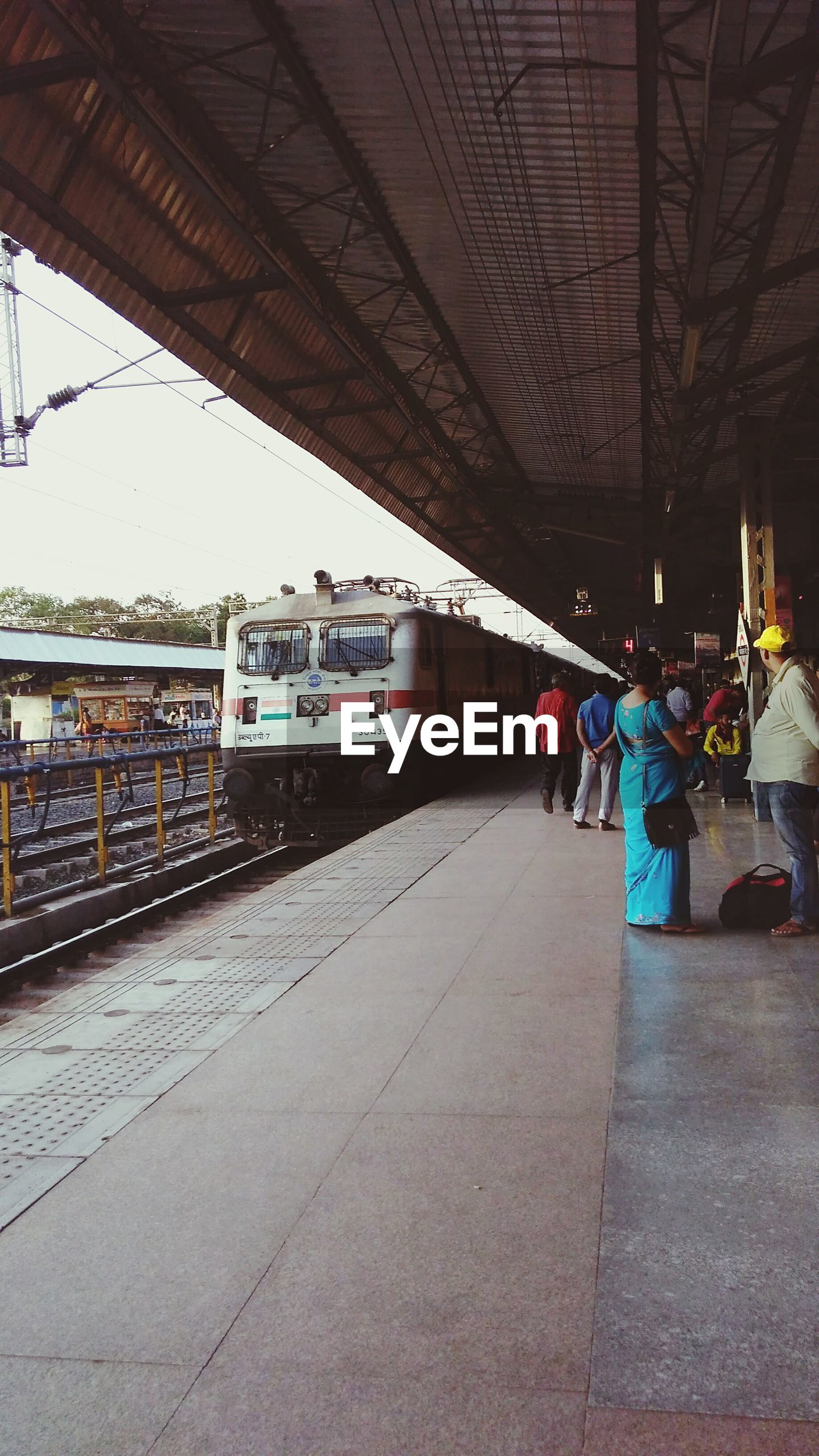 transportation, real people, bridge - man made structure, public transportation, built structure, connection, railroad station platform, mode of transport, men, rail transportation, architecture, day, railroad station, train - vehicle, full length, large group of people, women, outdoors, city, sky, people