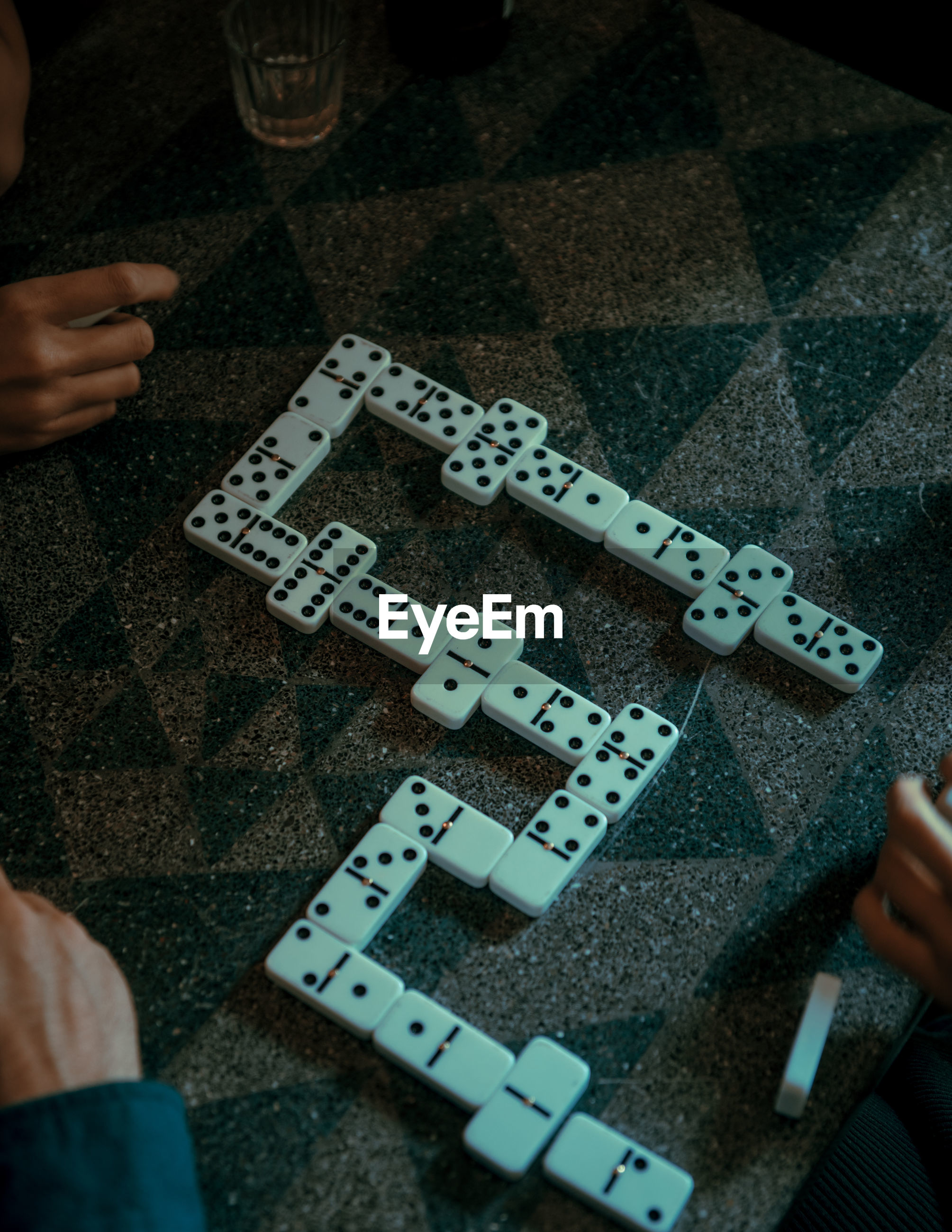 Cropped hands of friends playing dominoes on floor