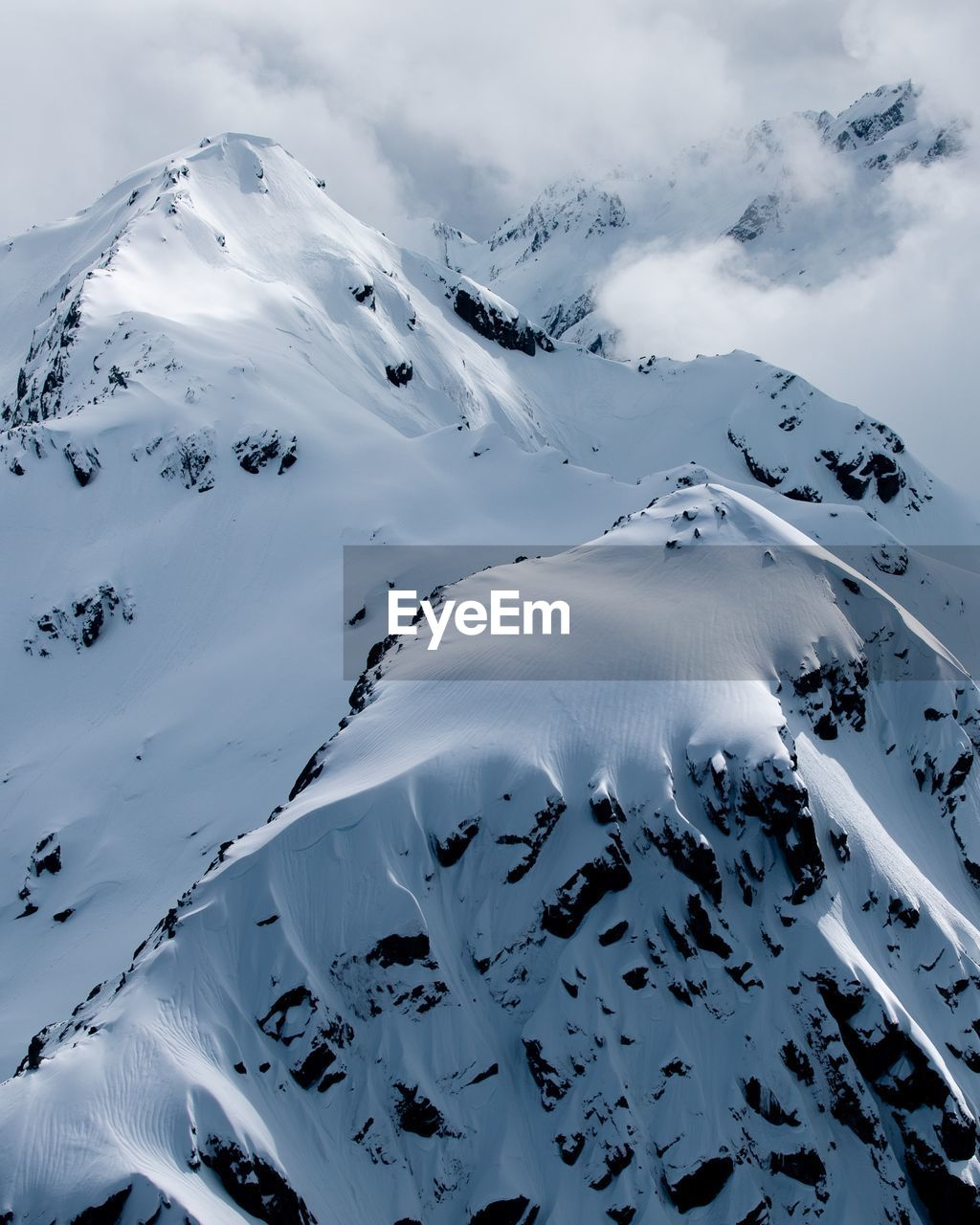 AERIAL VIEW OF SNOWCAPPED MOUNTAIN AGAINST SKY