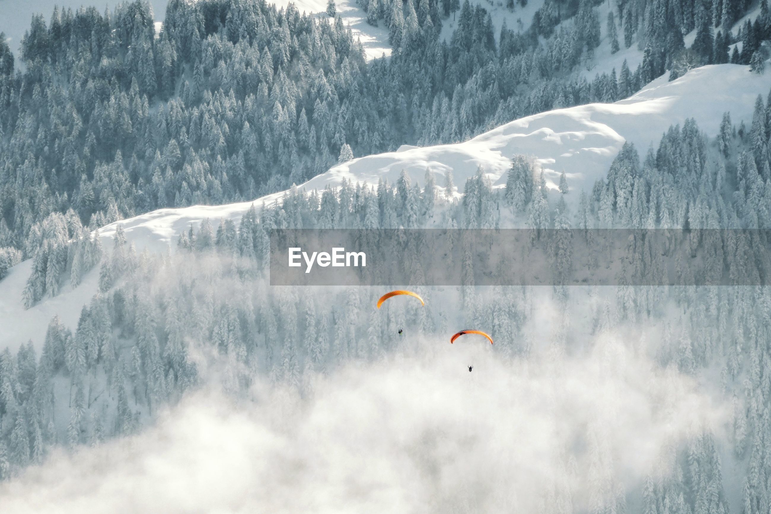 People flying over snowcapped mountain