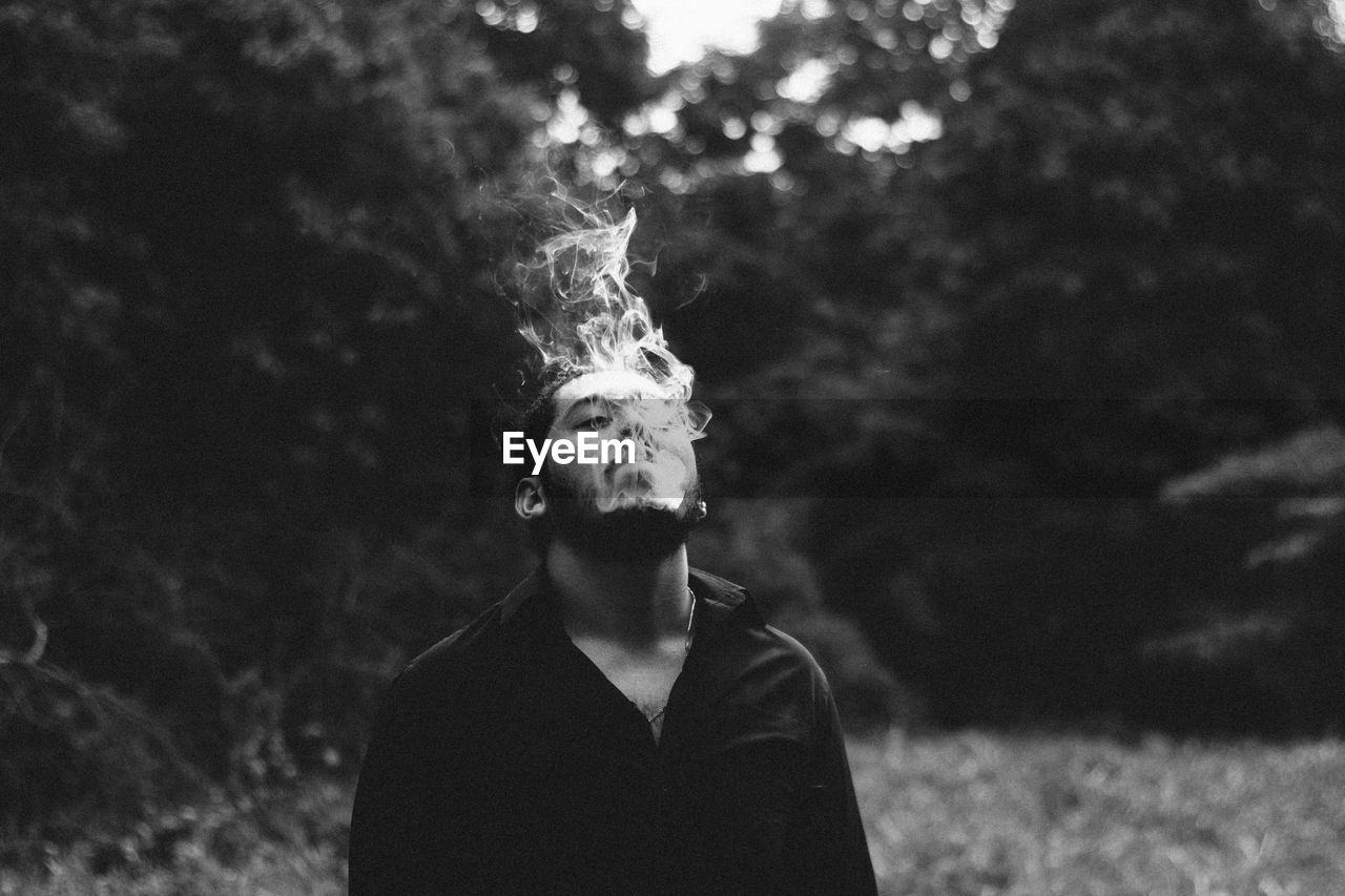 one person, leisure activity, real people, lifestyles, front view, young adult, headshot, focus on foreground, portrait, tree, smoke - physical structure, young men, warning sign, bad habit, social issues, nature, outdoors
