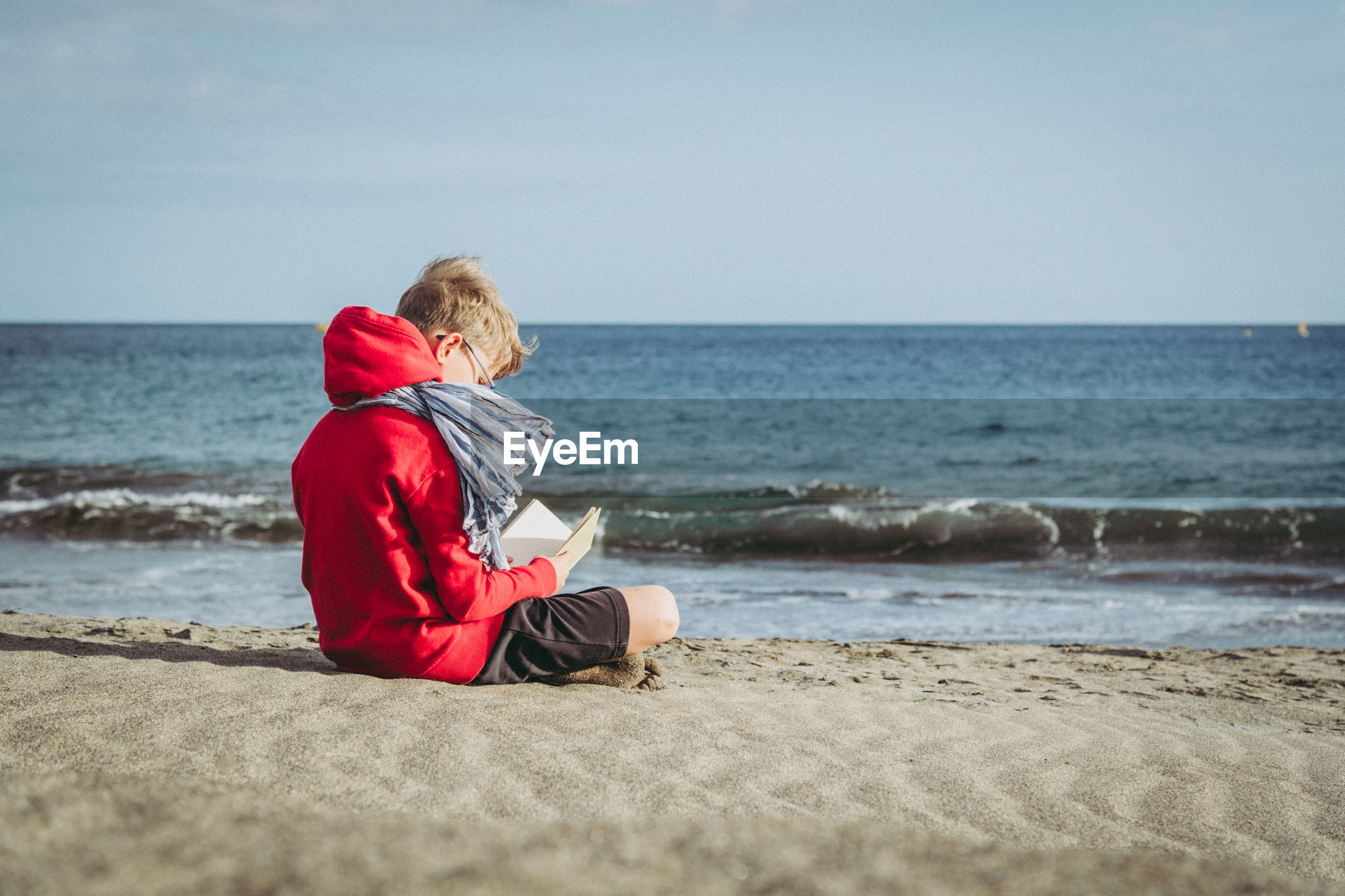 Boy reading book while sitting at beach against sky