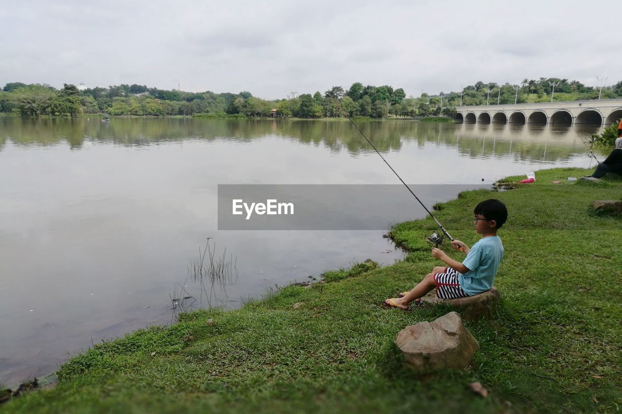 Side View Of Boy Fishing In Lake While Sitting On Rock At Field