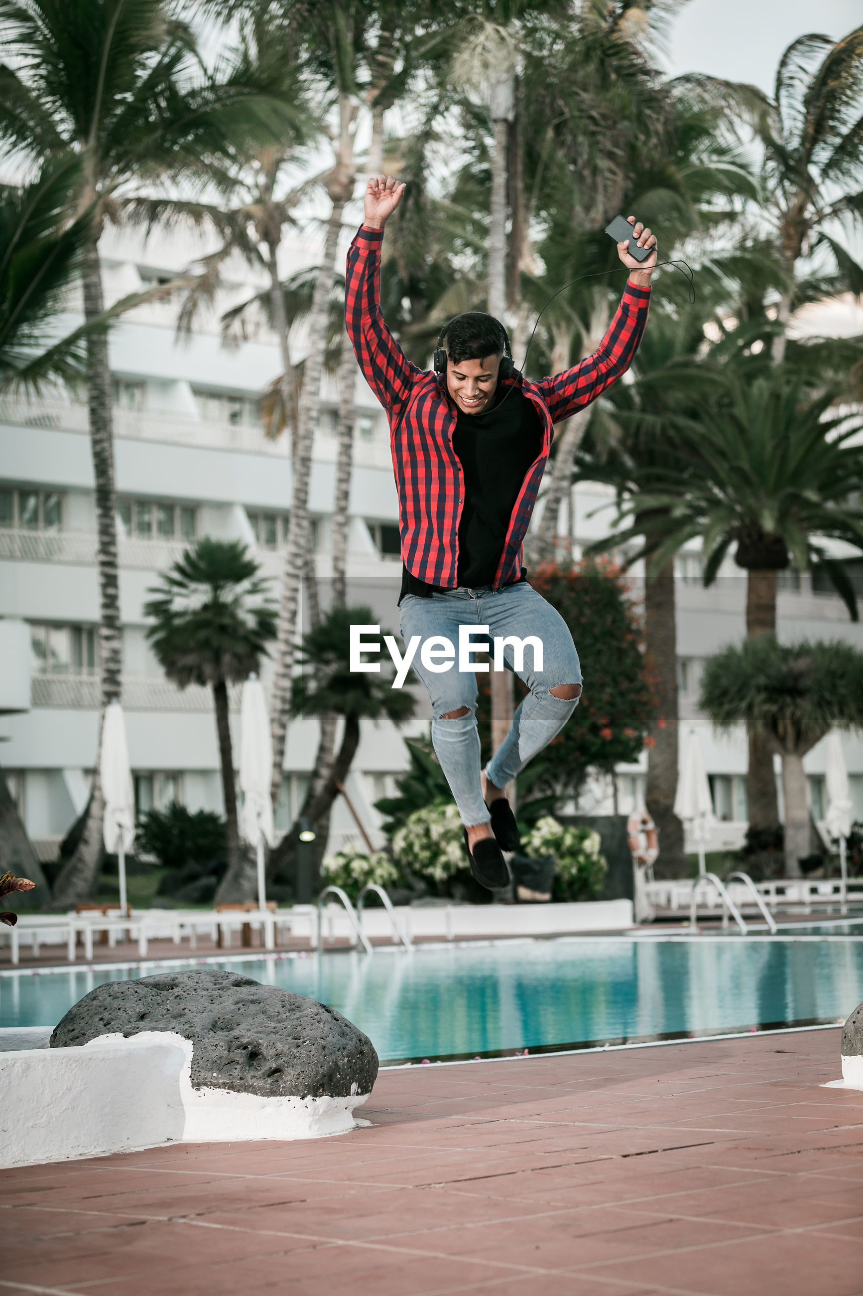 Man jumping by swimming pool
