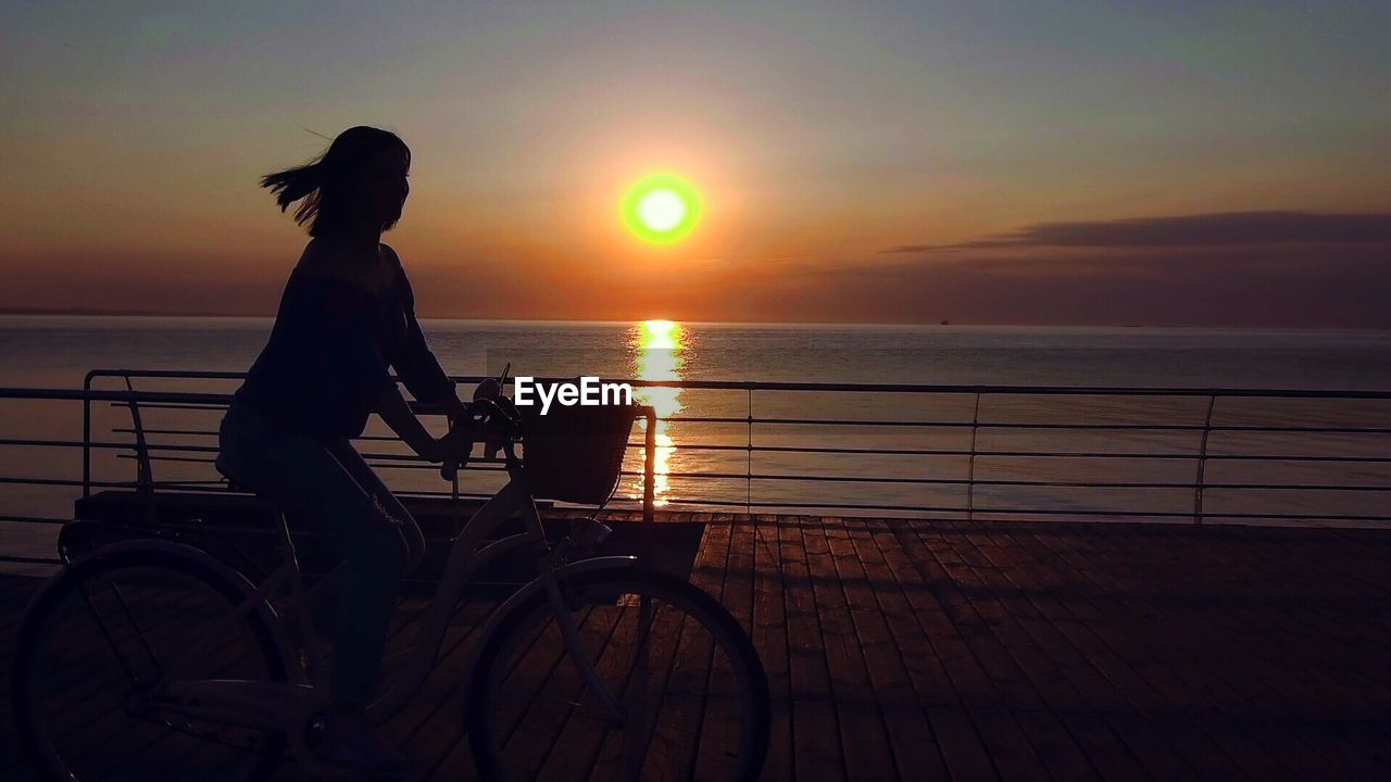 Silhouette woman riding bicycle on promenade against sky during sunset