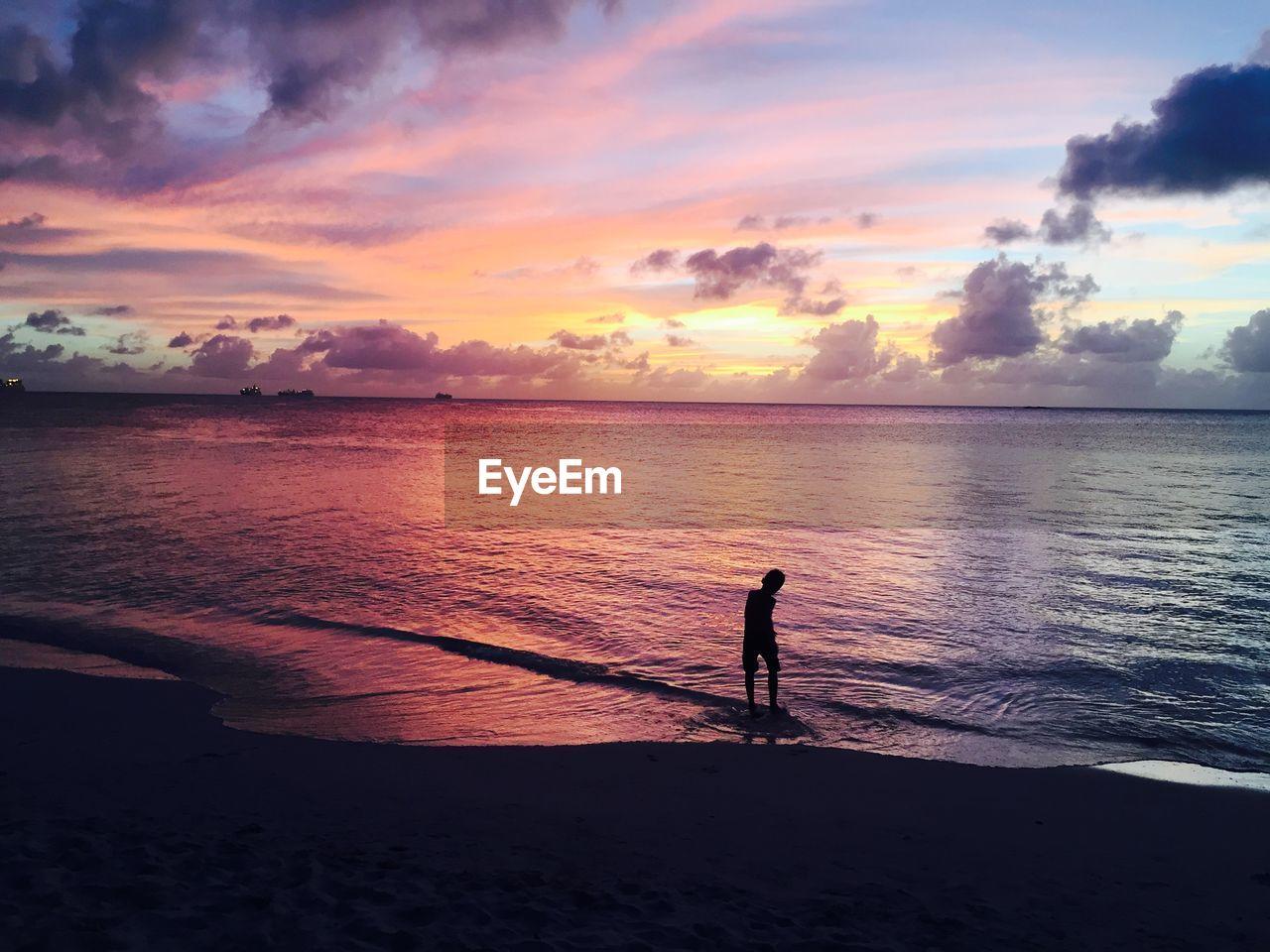 Man Standing On Sandy Beach
