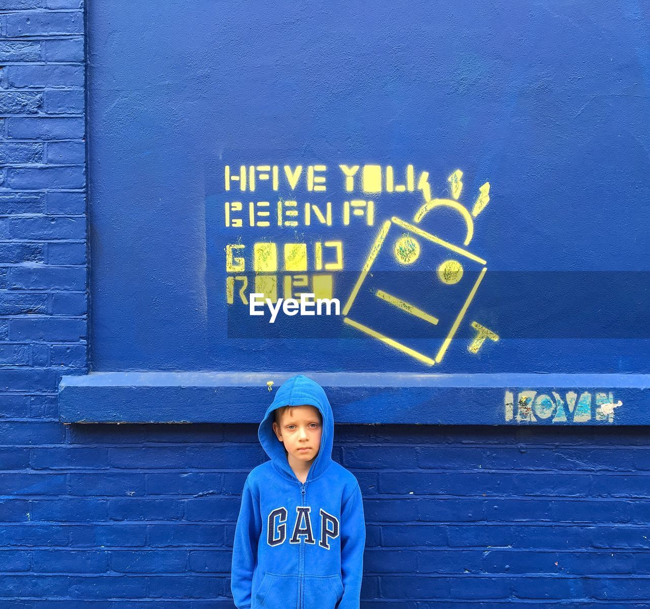 text, western script, blue, communication, day, outdoors, building exterior, boys, built structure, architecture, childhood, hooded shirt, real people, one person, portrait, standing, people