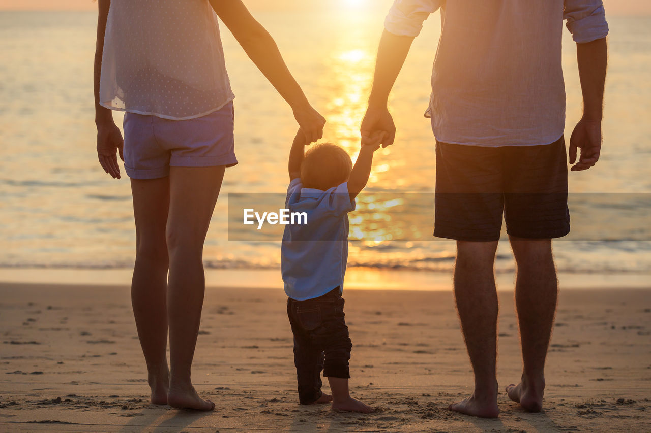 Low section of parents holding son hand while standing at beach during sunset