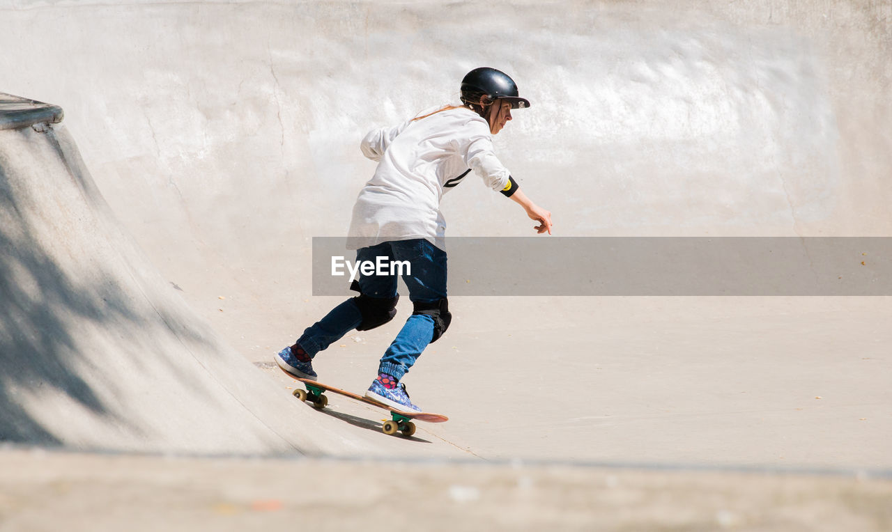 full length, sport, leisure activity, one person, lifestyles, skill, day, men, motion, real people, casual clothing, boys, child, childhood, skateboard park, sports equipment, helmet, balance, males, outdoors