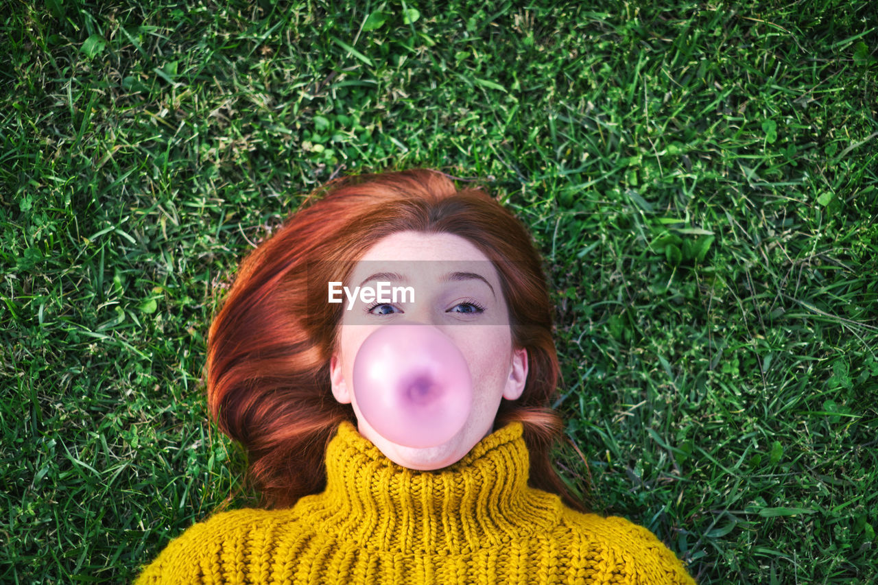 Portrait of woman blowing bubble gum while lying on grassy land