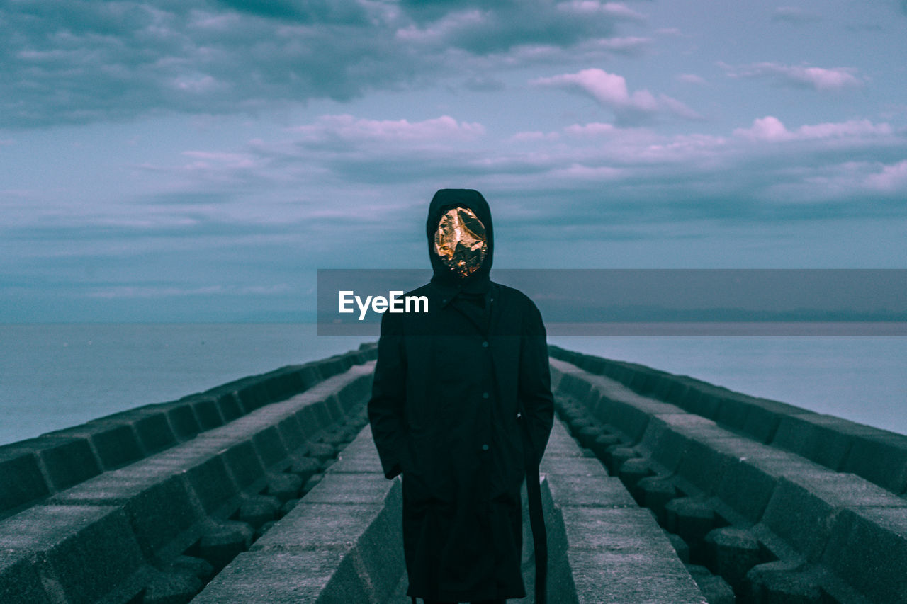 Man wearing mask while standing against sea and sky