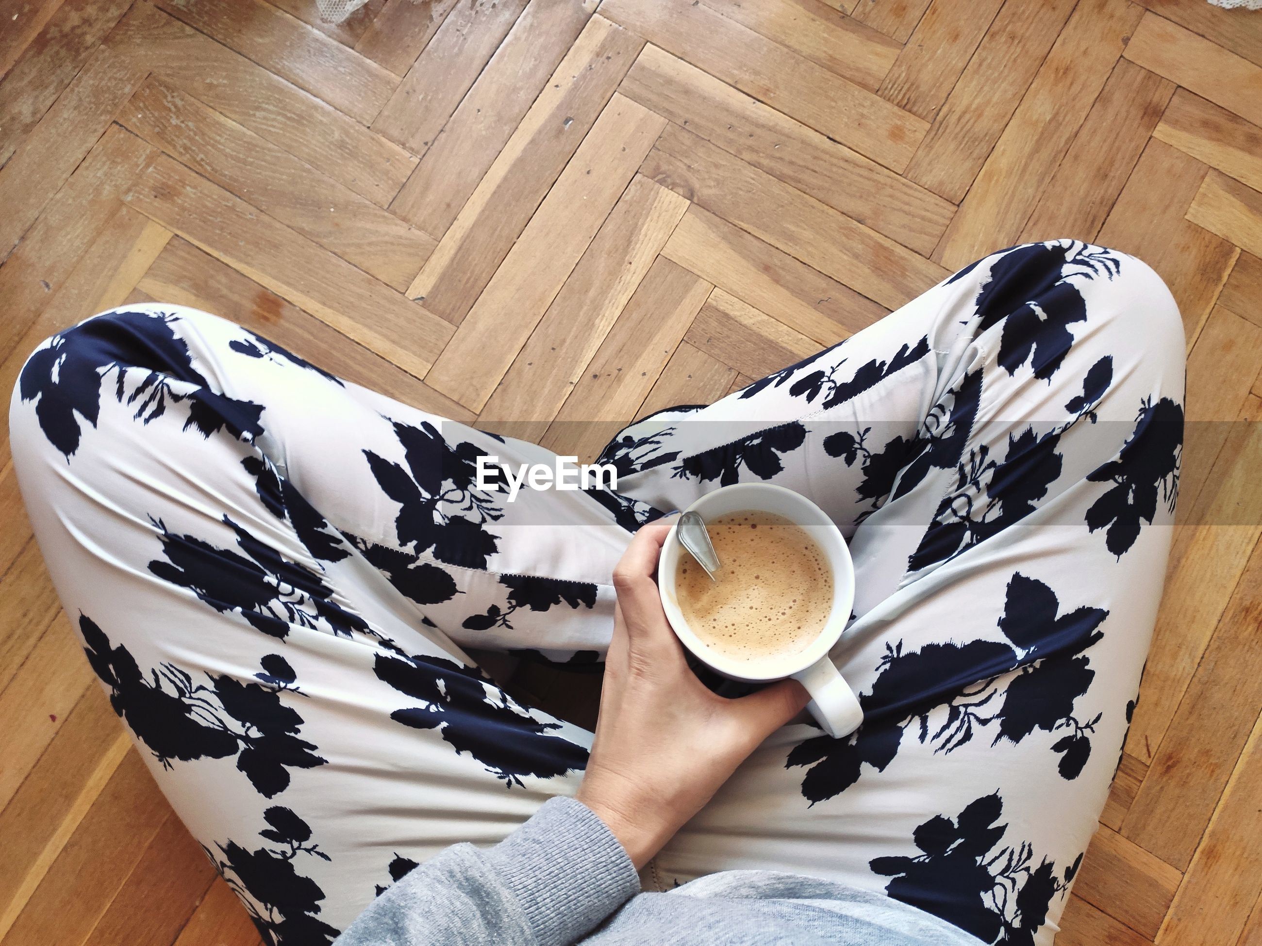 HIGH ANGLE VIEW OF COFFEE CUP ON HARDWOOD FLOOR
