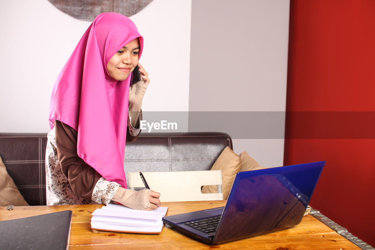Young Woman Talking On Mobile Phone While Using Laptop At Home