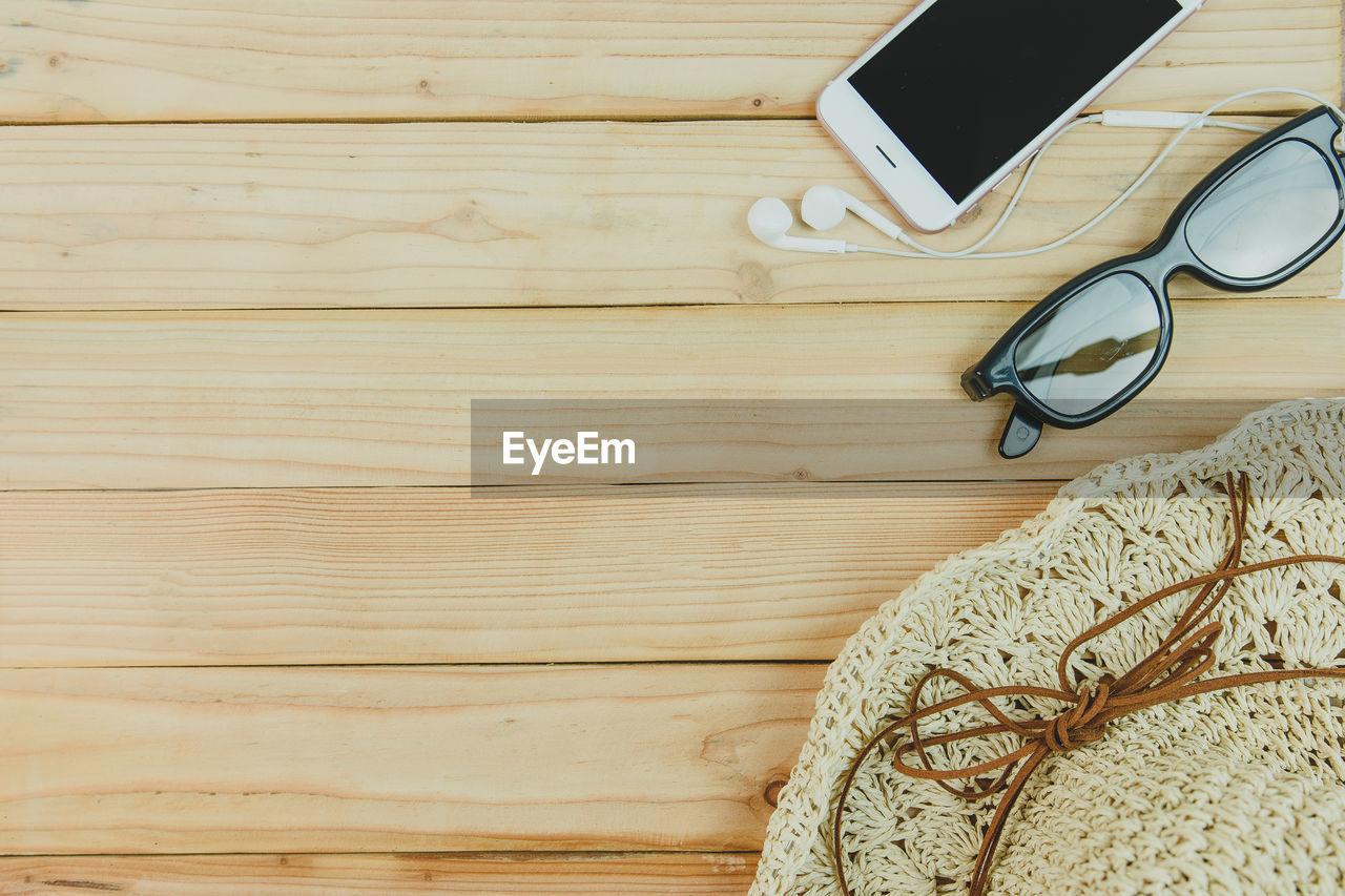 still life, wood - material, indoors, glasses, no people, close-up, pattern, table, high angle view, eyeglasses, directly above, technology, fashion, connection, textile, brown, wireless technology, communication, personal accessory, art and craft, warm clothing