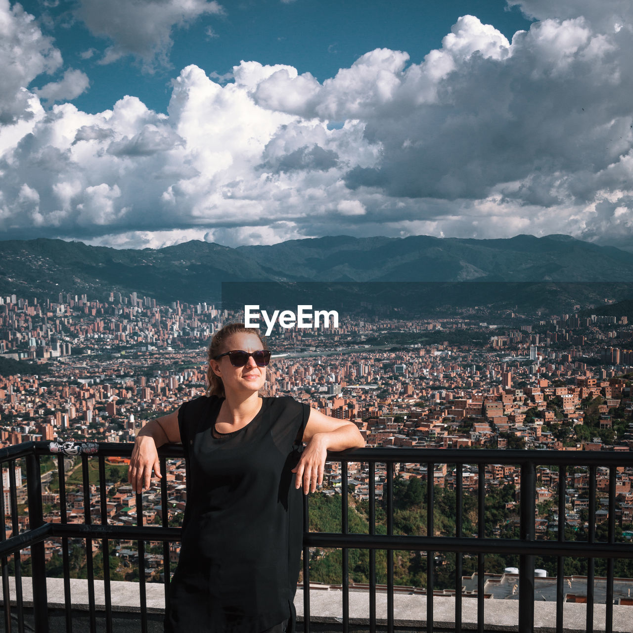 Woman standing at building balcony with city in background against cloudy sky