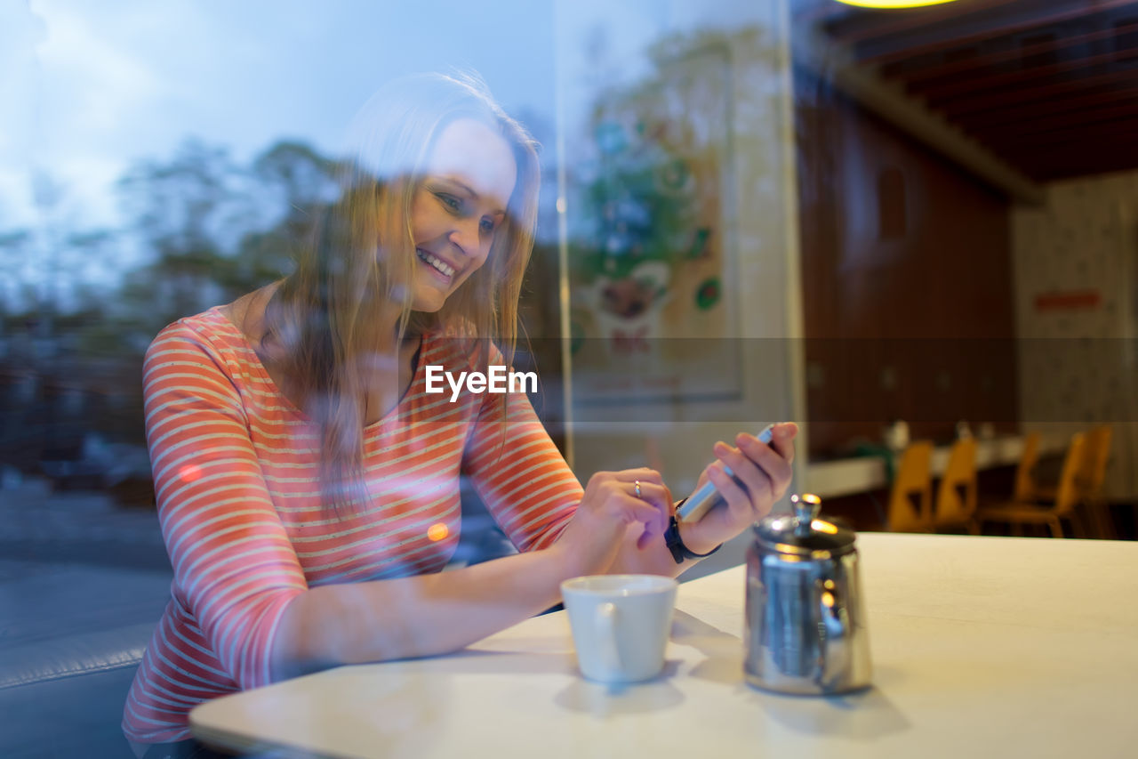 drink, food and drink, real people, cup, young adult, one person, lifestyles, table, smiling, coffee - drink, coffee, mug, coffee cup, young women, refreshment, women, leisure activity, happiness, sitting, beautiful woman, hair, hairstyle, outdoors