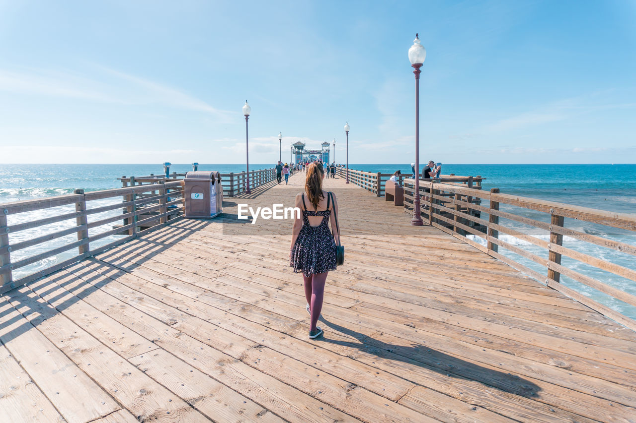 Rear View Of Woman Walking On Pier Over Sea Against Sky
