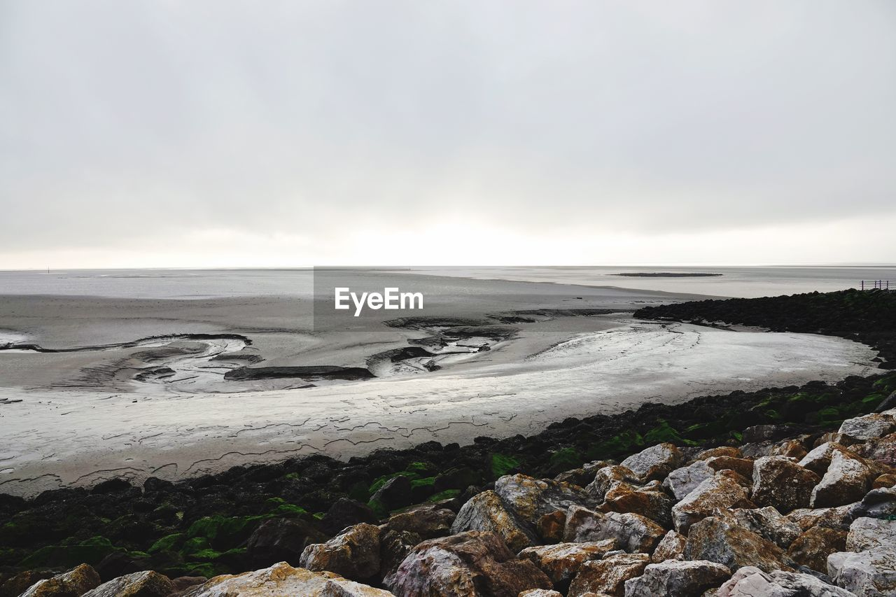 water, beauty in nature, sky, scenics - nature, sea, beach, tranquil scene, tranquility, solid, rock, nature, land, no people, rock - object, cloud - sky, day, non-urban scene, horizon, outdoors, horizon over water, power in nature, rocky coastline