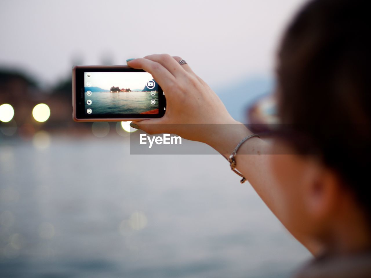 Close-Up Of Woman Photographing With Mobile Phone By Lake