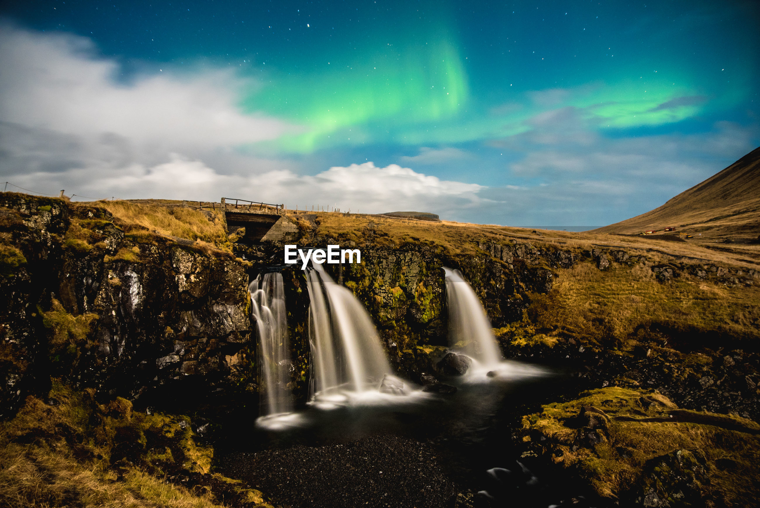 Scenic view of waterfall against night sky with aurora borealis