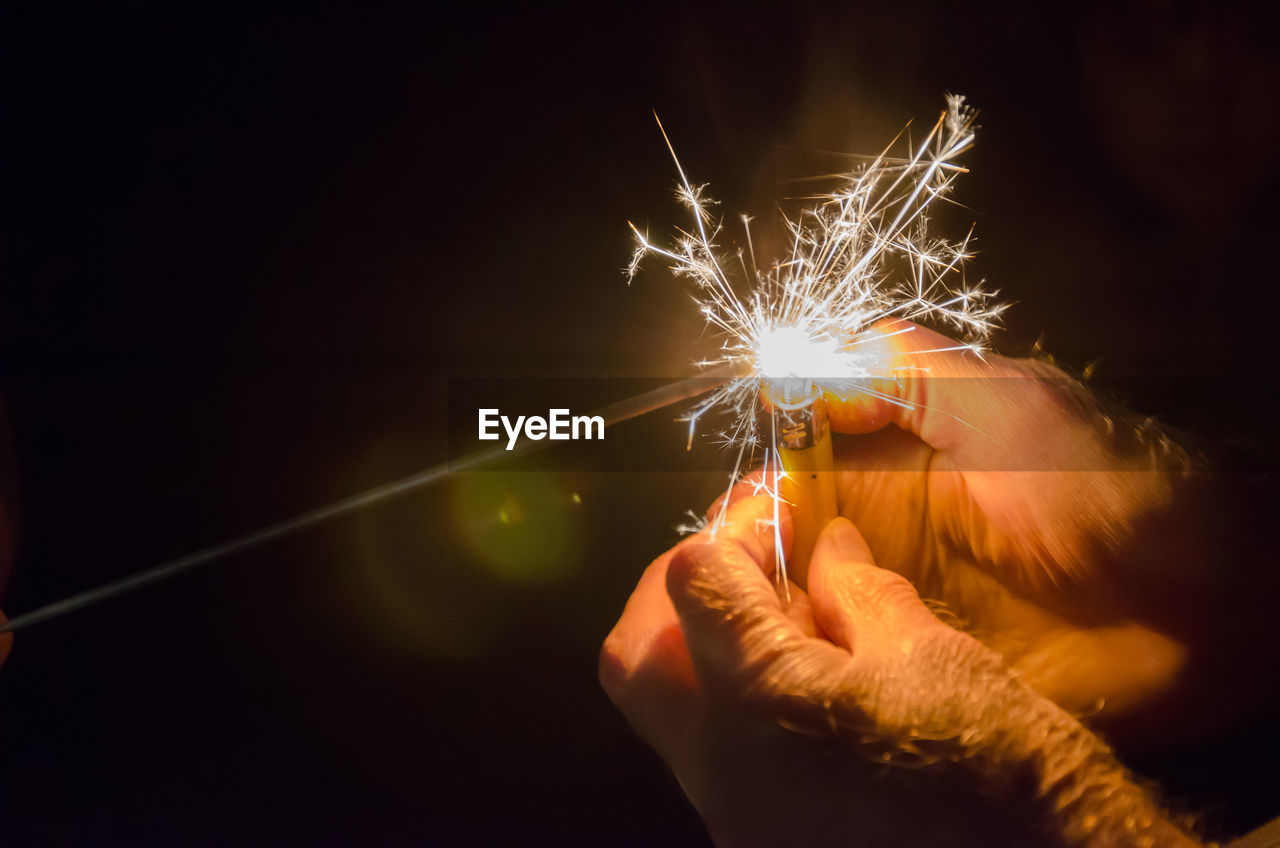 Cropped hands of man igniting sparkler with cigarette lighter at night