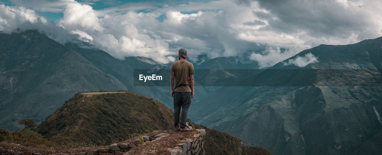 Rear View Of Young Man Looking At Mountains While Standing Against Cloudy Sky