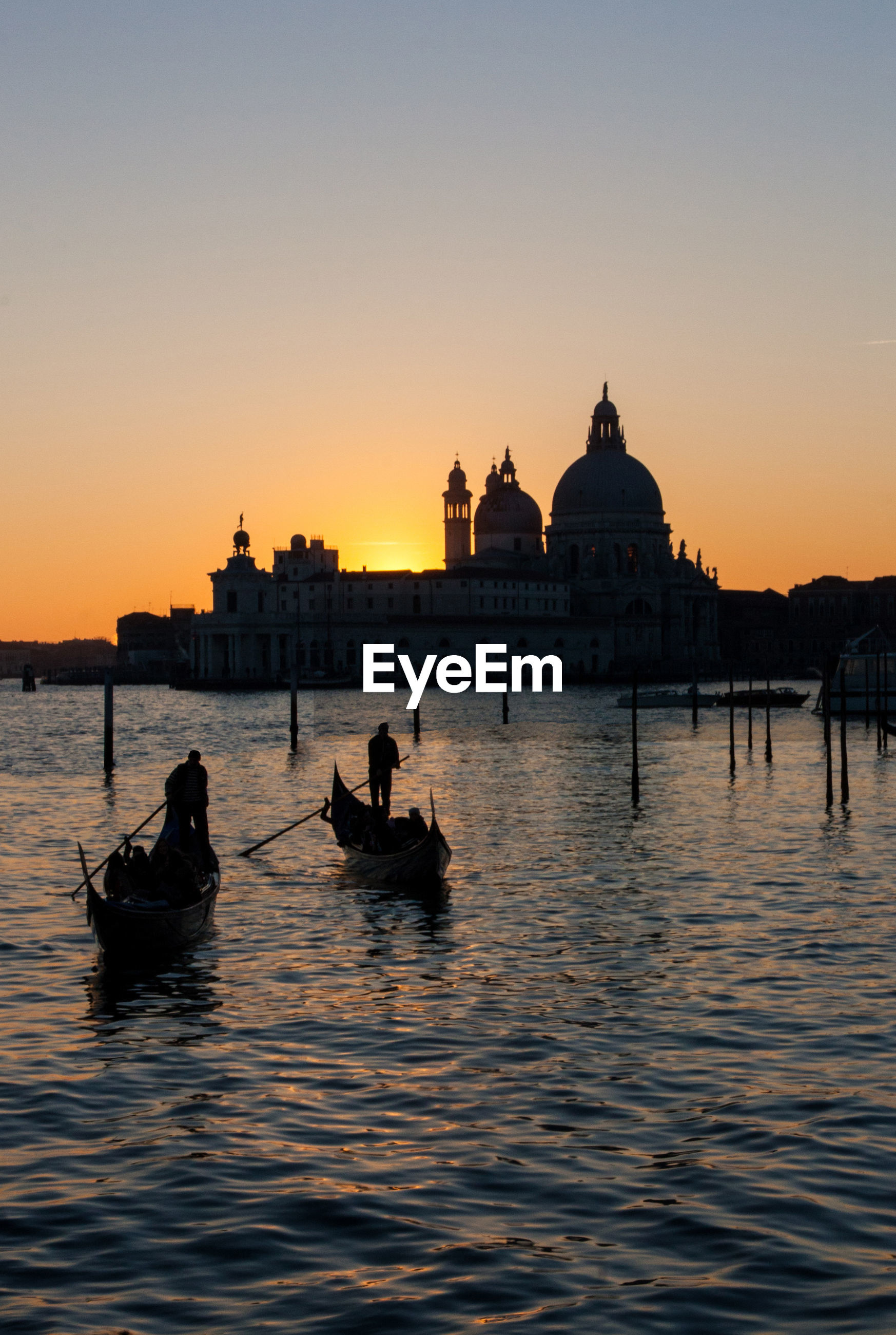 Gondoliers sailing on grand canal against santa maria della salute during sunset